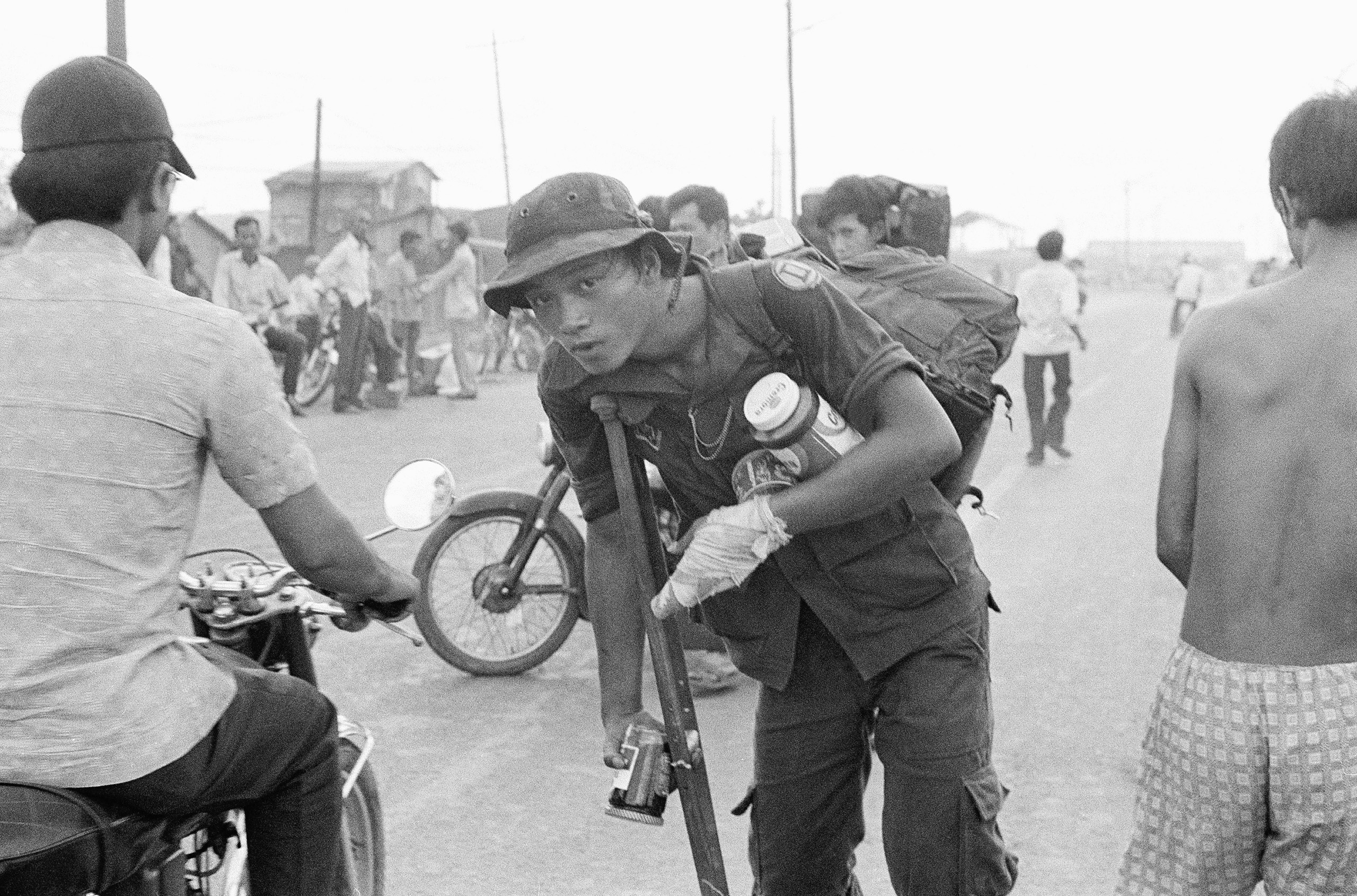 A crippled South Vietnamese war veteran limps away on crutch with food looted from abandoned U.S. installations after the evacuation of Saigon.