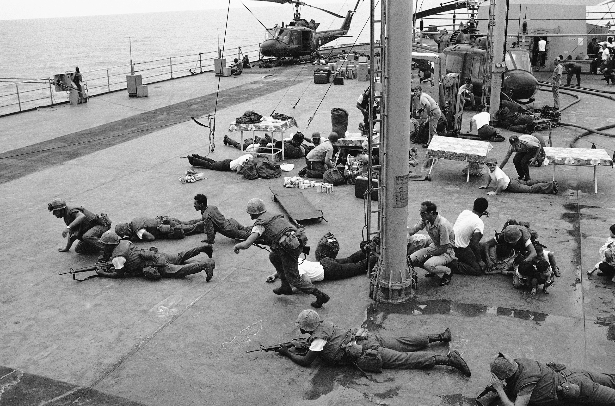 U.S. Marines hit the deck of the USS Blue Ridge to dodge flying metal from a South Vietnamese helicopter that crashed on the deck of the ship. One pilot had dropped his helicopter on the blade of another, and chunks of metal ripped through the air. The top helicopter, with its load of women and children, nearly toppled into the sea, but they were rescued without injury.