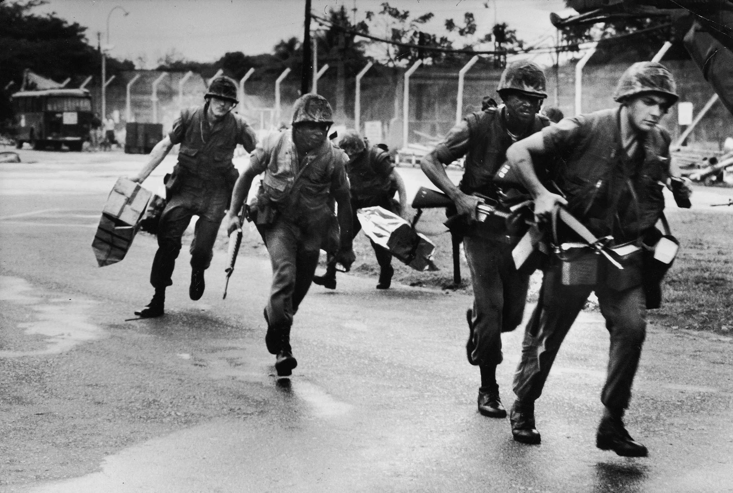 Helicopter-transported U.S. Marines running, arriving at Tan Son Nhut air base to secure area around Defense Attaché Office compound for evacuation of the last Americans in Saigon.