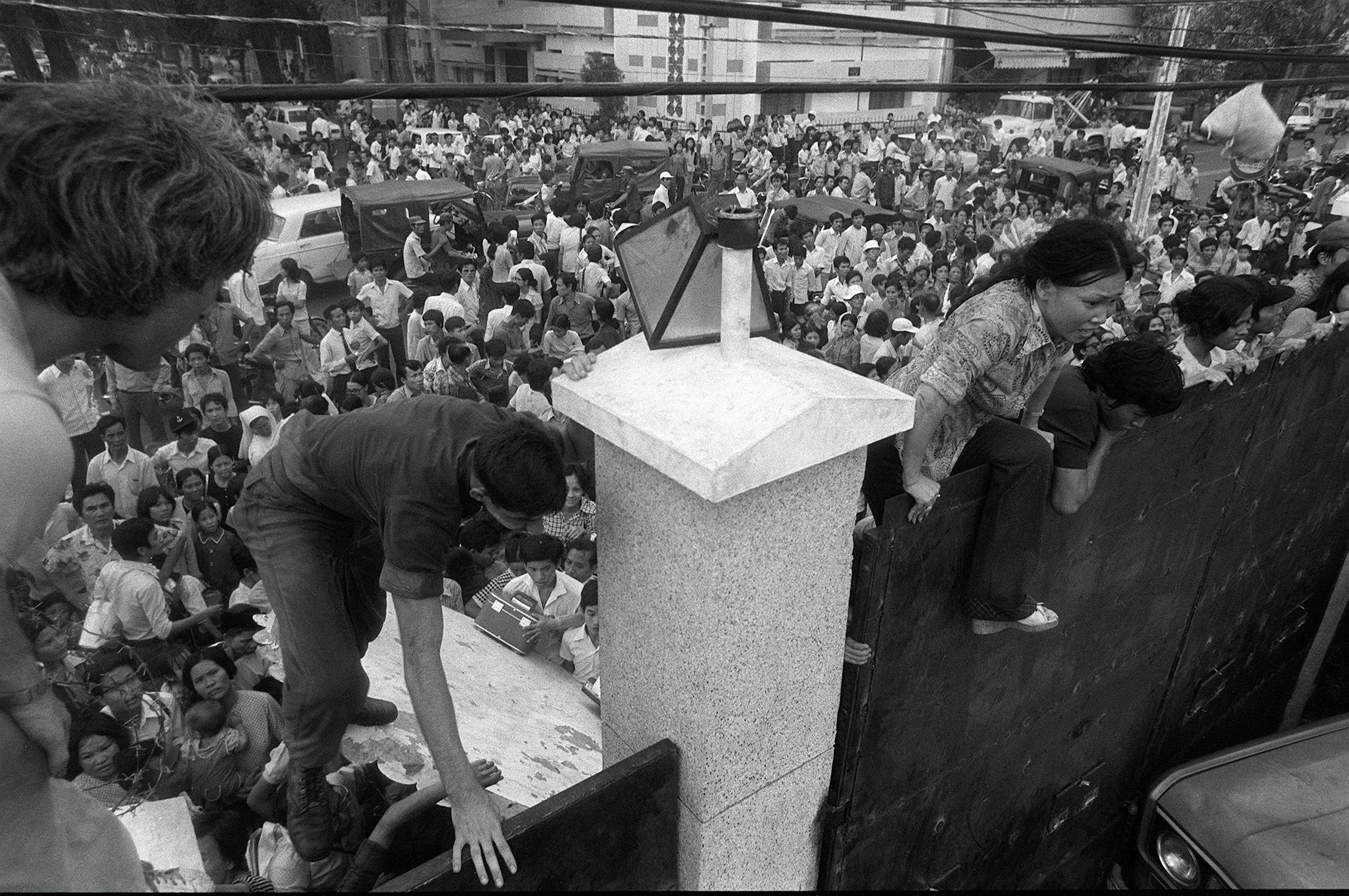 Mobs of South Vietnamese civilians scale the 14-foot wall of the U.S. Embassy trying to reach evacuation helicopters as the last Americans departed from Vietnam.