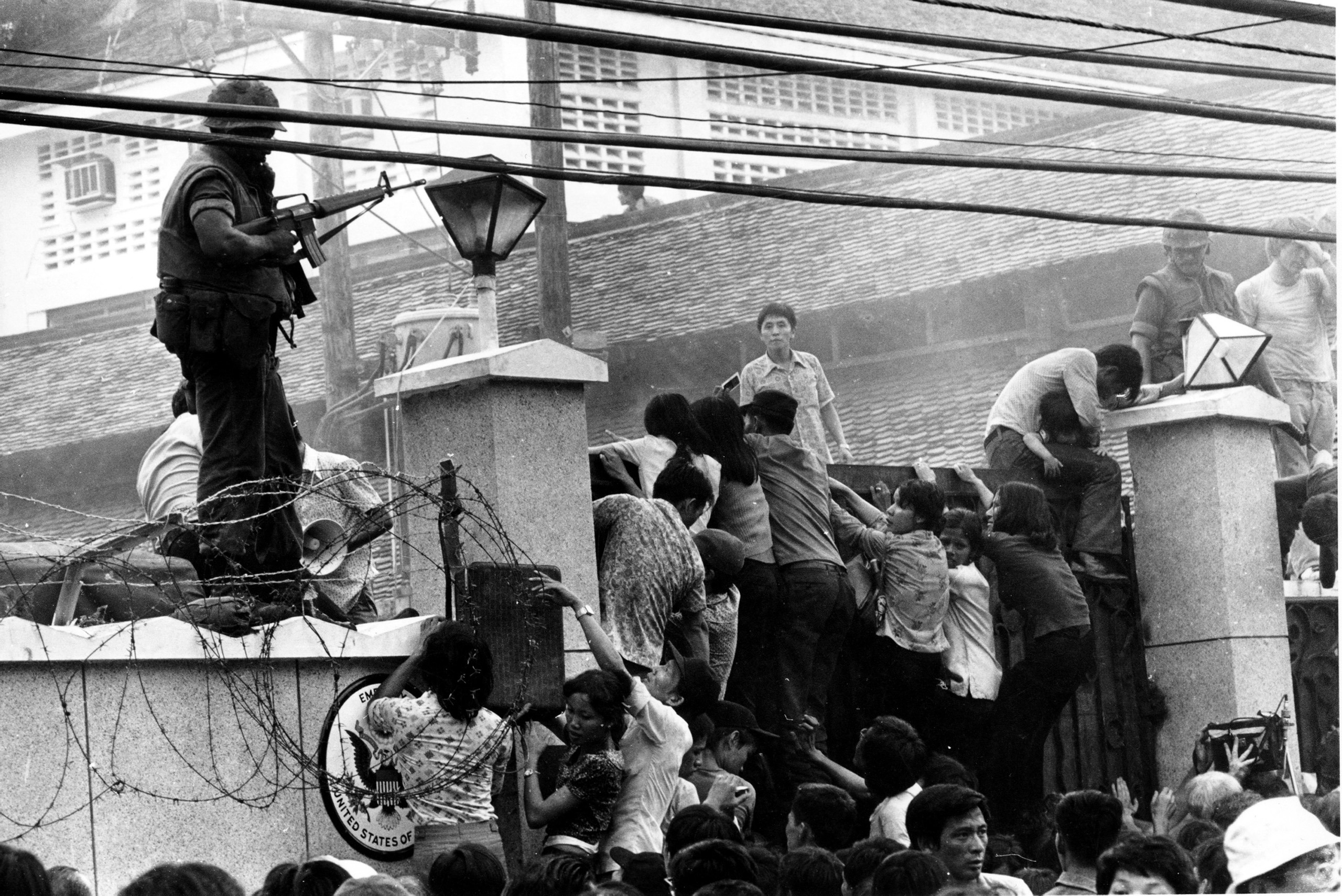 Citizens scale the wall of the U.S. Embassy in Saigon, trying to get to the helicopter pickup zone.