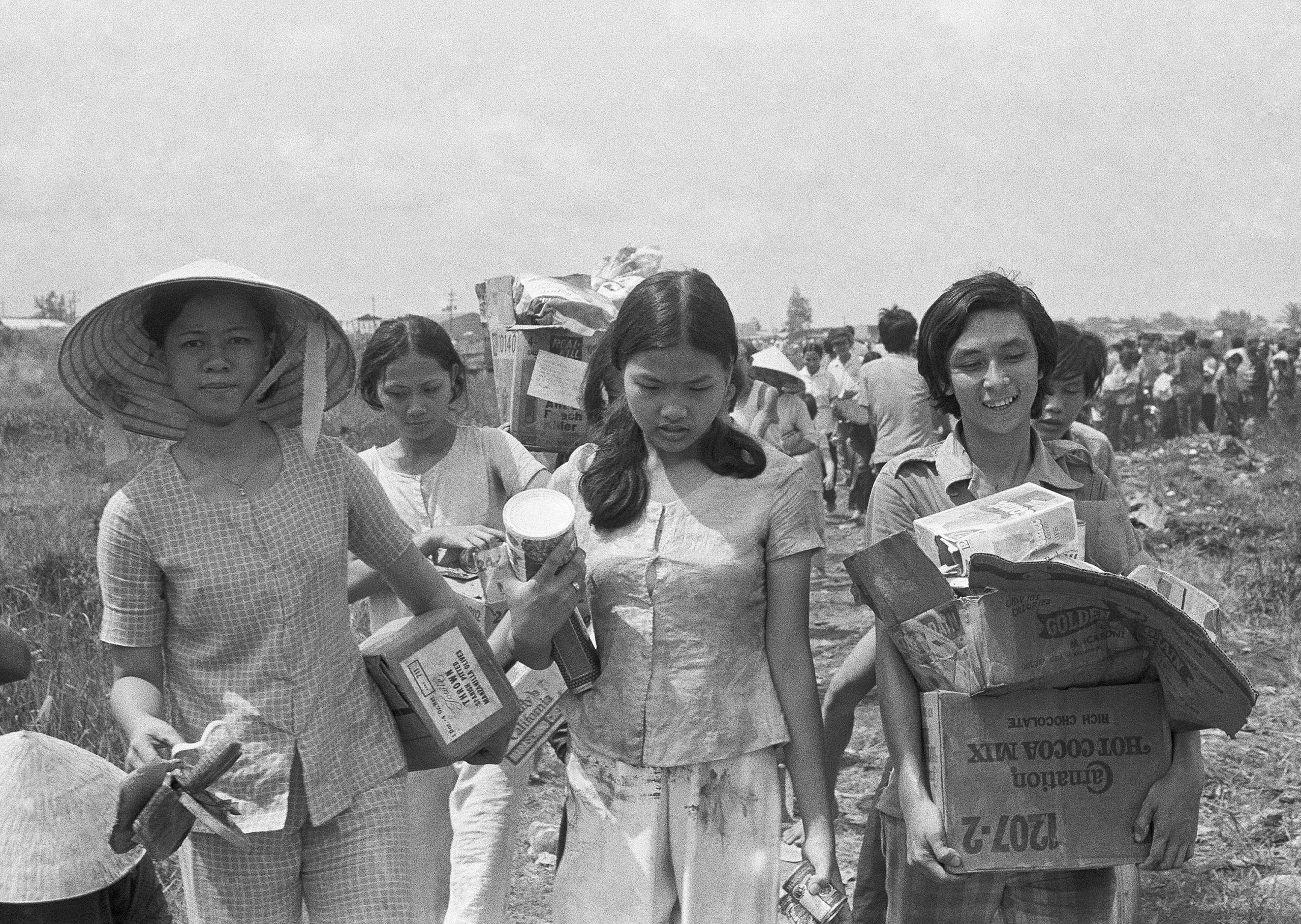 Vietnamese women clutch boxes of food looted from U.S. installation after the evacuation of Saigon.