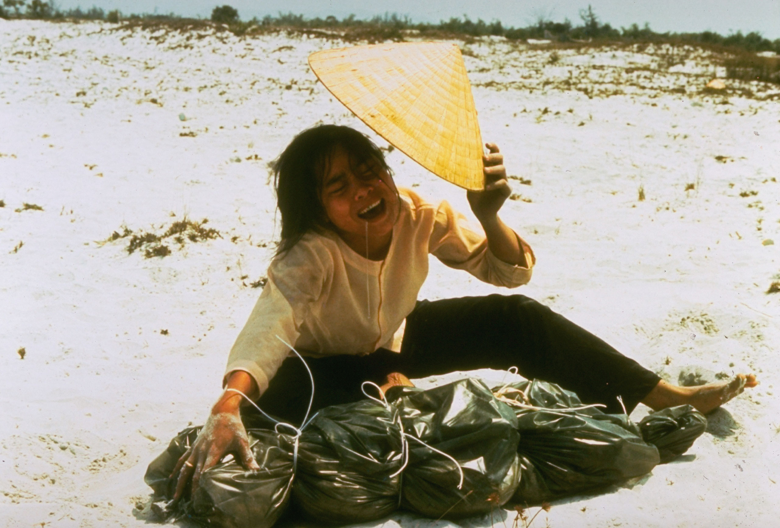 A grieving widow cries over a plastic bag containing remains of her husband which were found in mass grave. He was killed during the Tet offensive in 1968.