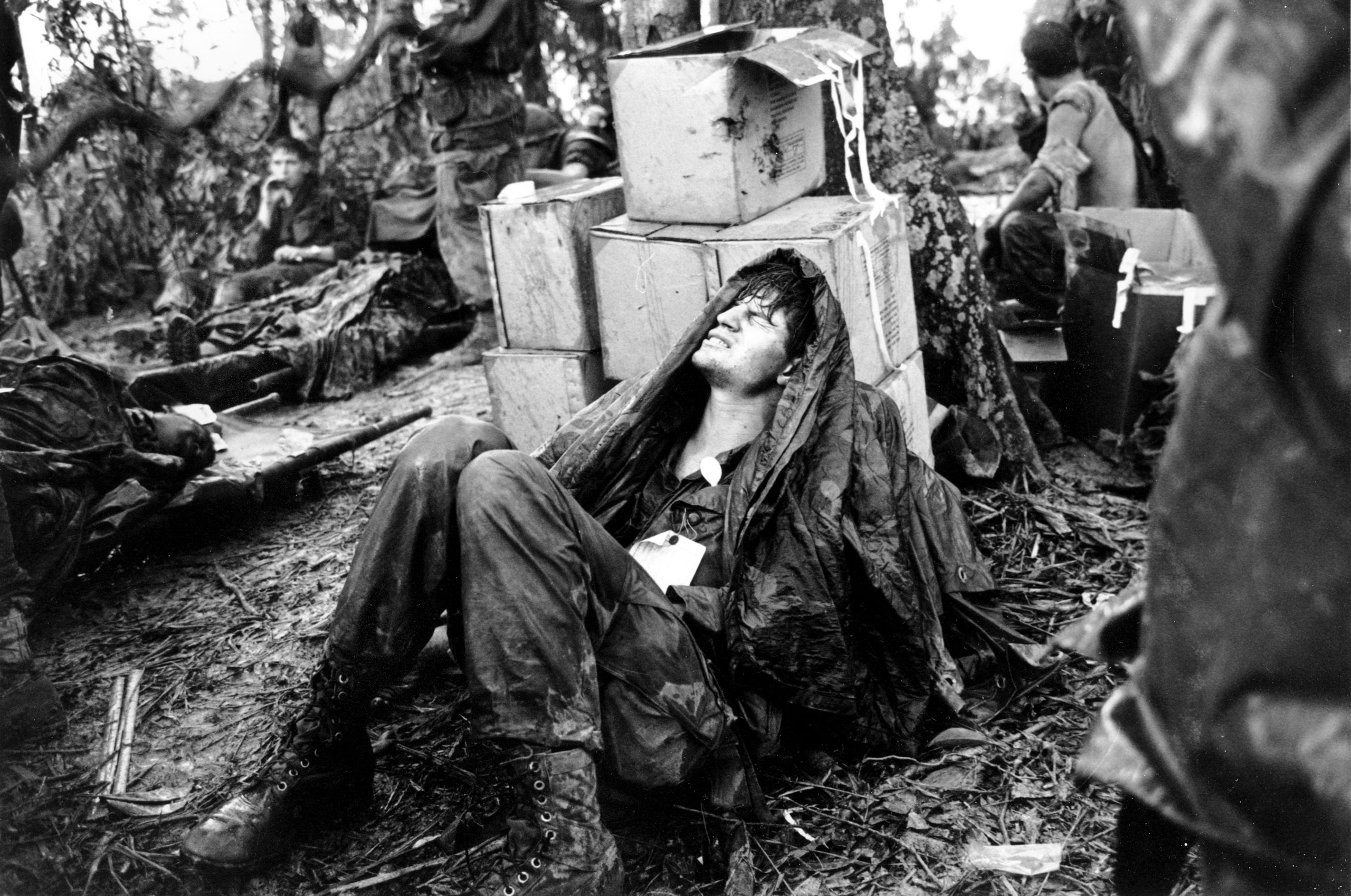 A wounded U.S. paratrooper grimaces in pain as he awaits medical evacuation at base camp in the A Shau Valley near the Laos border in South Vietnam on May 19, 1969.