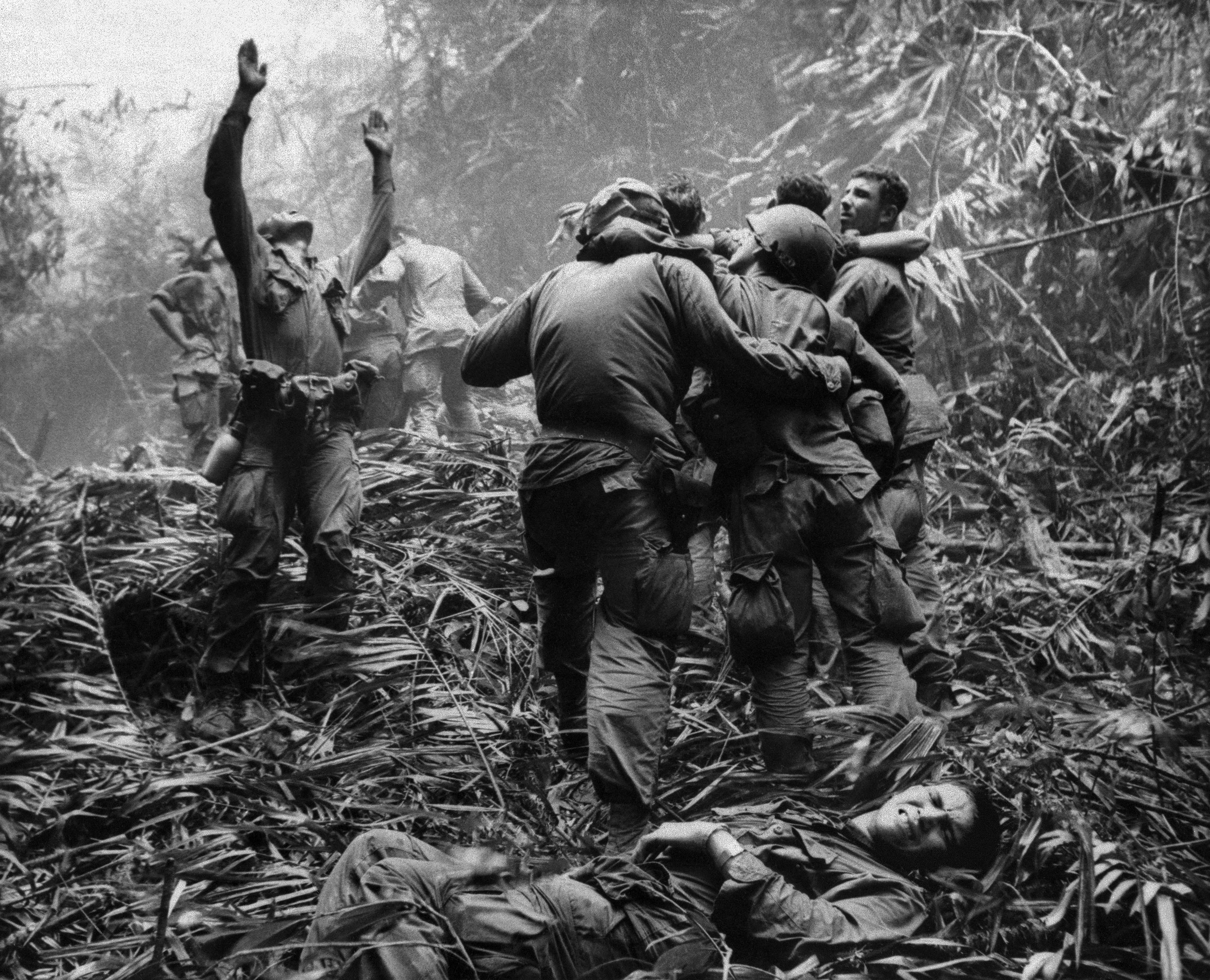 As fellow troopers aid wounded comrades, the first sergeant of A Company, 101st Airborne Division, guides a medevac helicopter through the jungle foliage to pick up casualties suffered during a five-day patrol near Hue in Vietnam in April 1968.