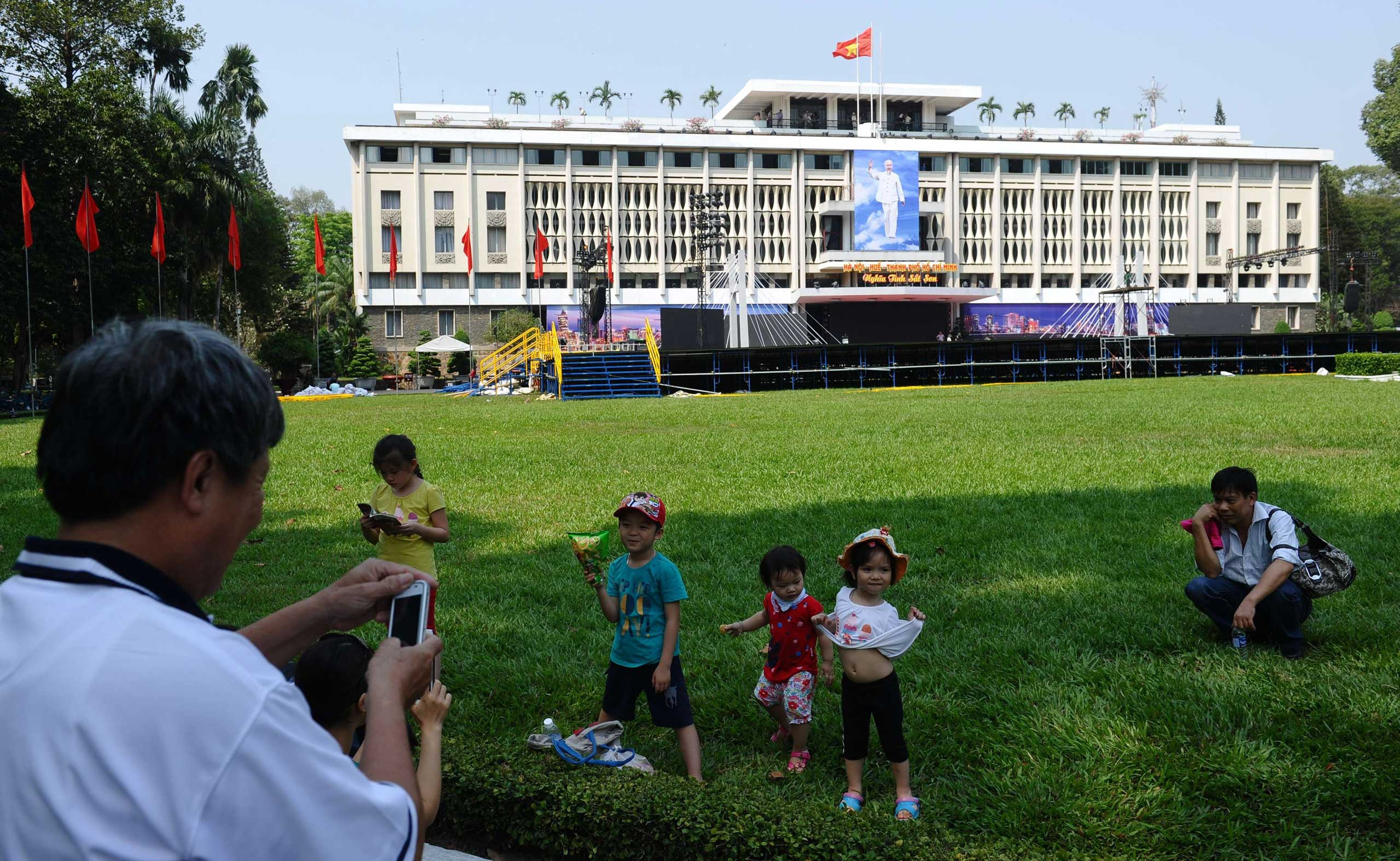 A man takes a family photo in front of the former presidential palace of the former South Vietnam U.S.-backed regime in Ho Chi Minh City, on April 10, 2015.