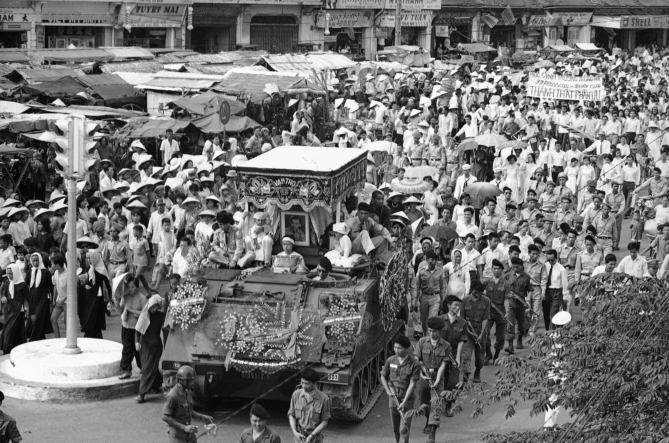 The body of a South Vietnamese captain is carried on an army tank surrounded by many soldiers and civilians in a funeral procession on Saigon's main street on Nov. 5, 1963.