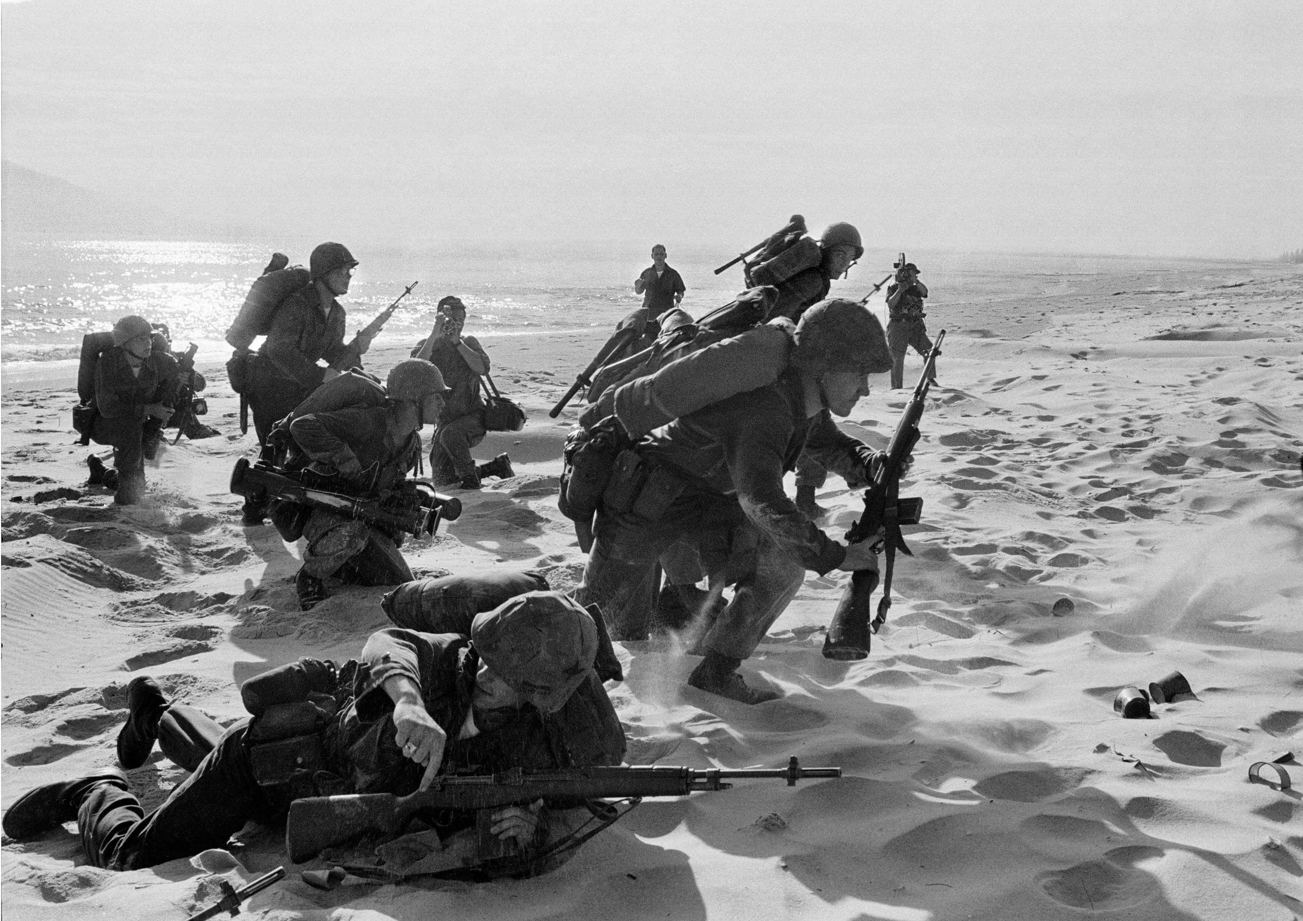 Newly landed U.S. Marines make their way through the sands of Red Beach at Da Nang, on their way to reinforce the air base, as South Vietnamese Rangers battled guerrillas about three miles south, on April 10, 1965.