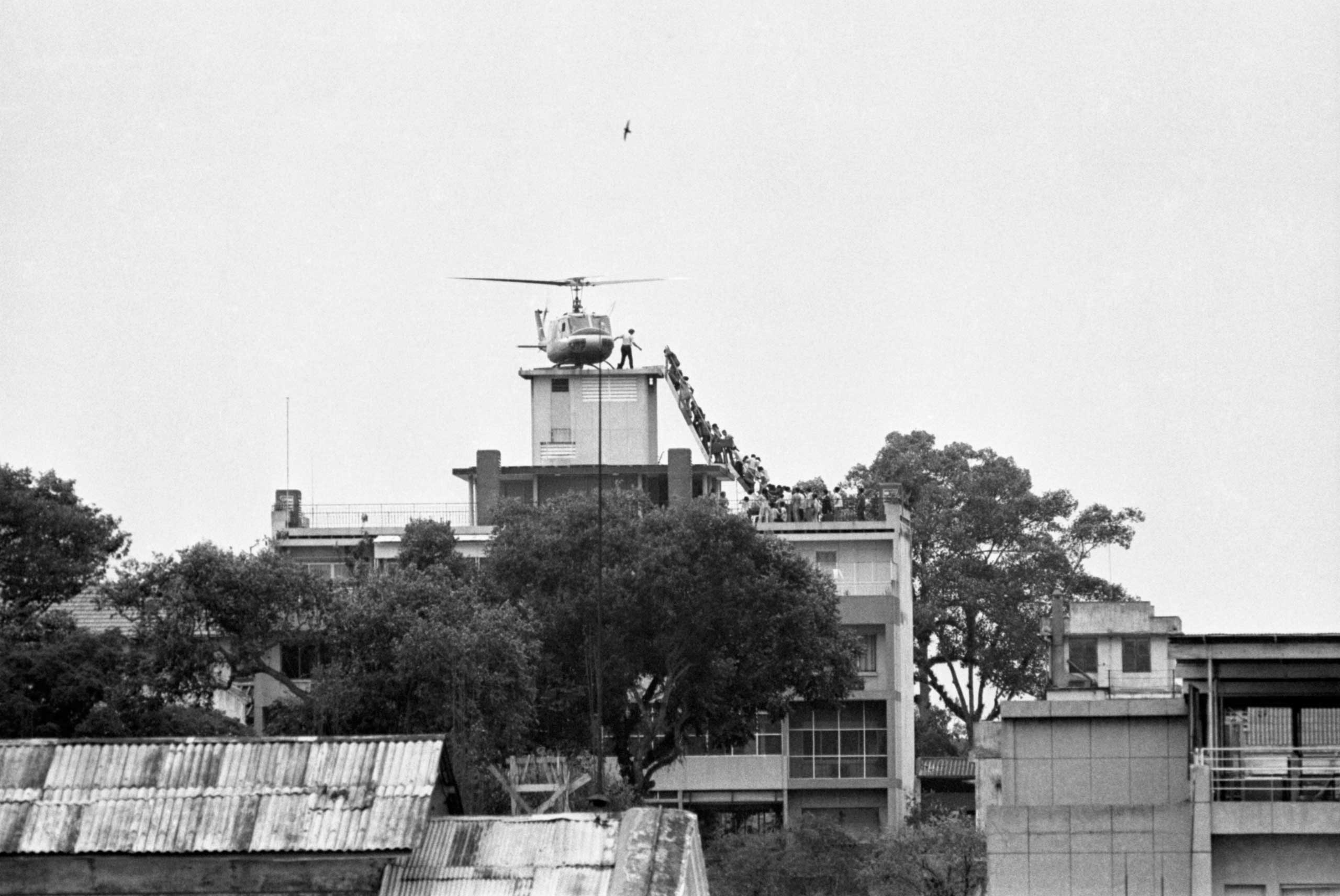 A CIA employee (probably O.B. Harnage) helps Vietnamese evacuees onto an Air America helicopter from the top of 22 Gia Long Street, a half mile from the U.S. Embassy on Apr. 25, 1975.