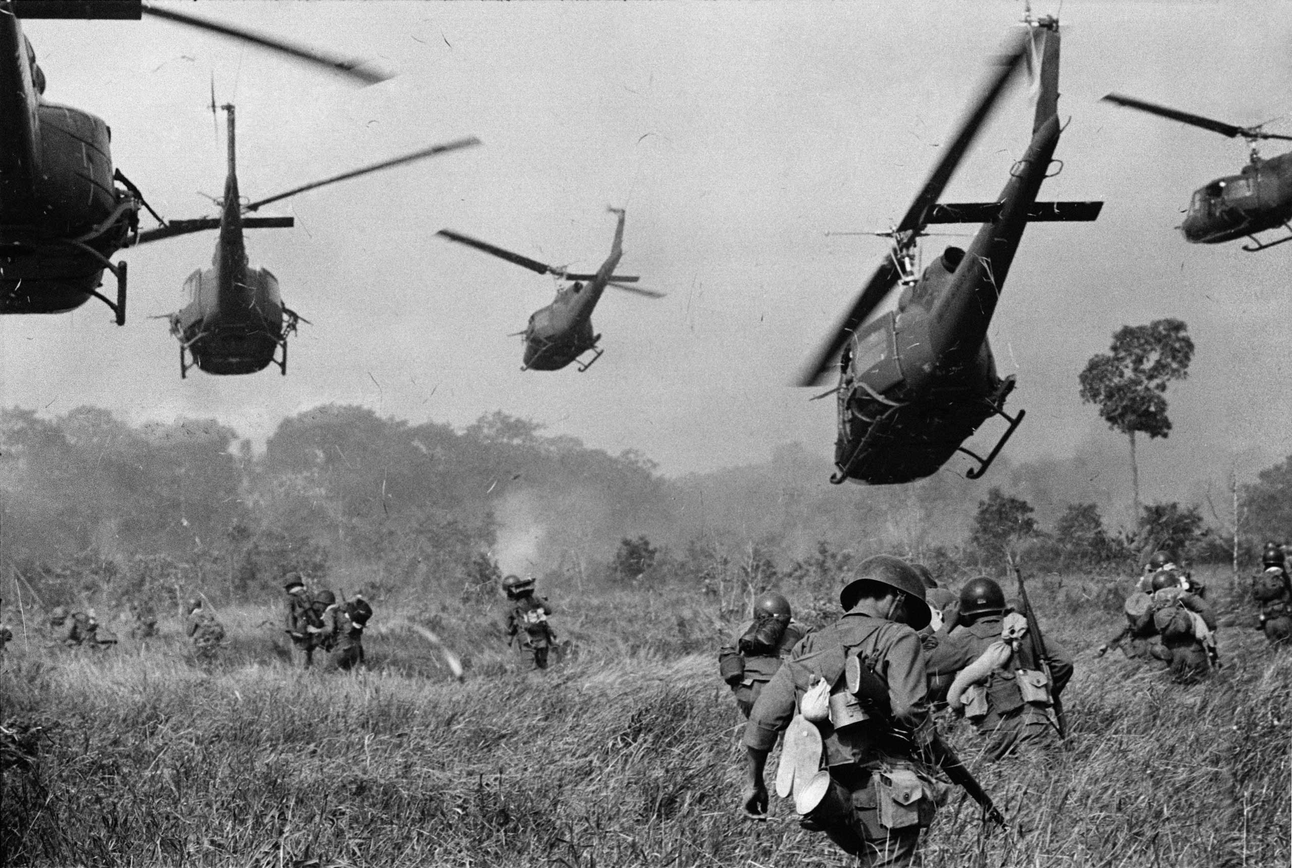 Hovering U.S. Army helicopters pour machine gun fire into the tree line to cover the advance of South Vietnamese ground troops in an attack on a Viet Cong camp 18 miles north of Tay Ninh, northwest of Saigon near the Cambodian border, in March 1965.