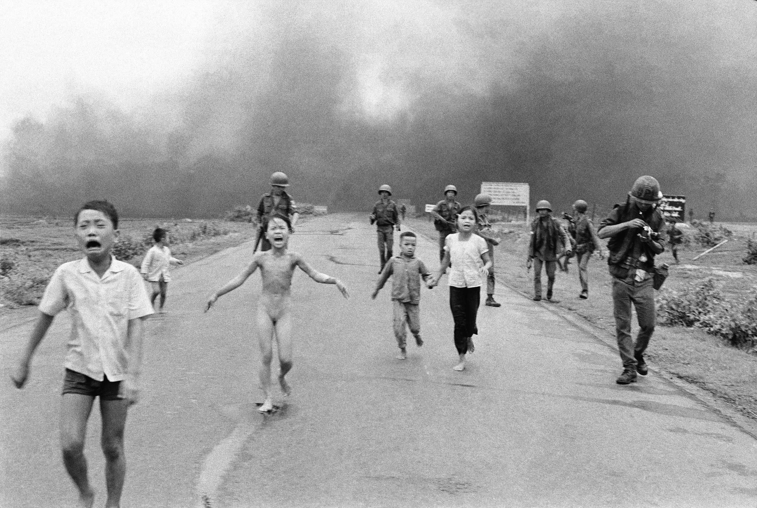 South Vietnamese forces follow after terrified children, including 9-year-old Kim Phuc (center) as they run down Route 1 near Trang Bang after an aerial napalm attack on suspected Viet Cong hiding places on June 8, 1972.