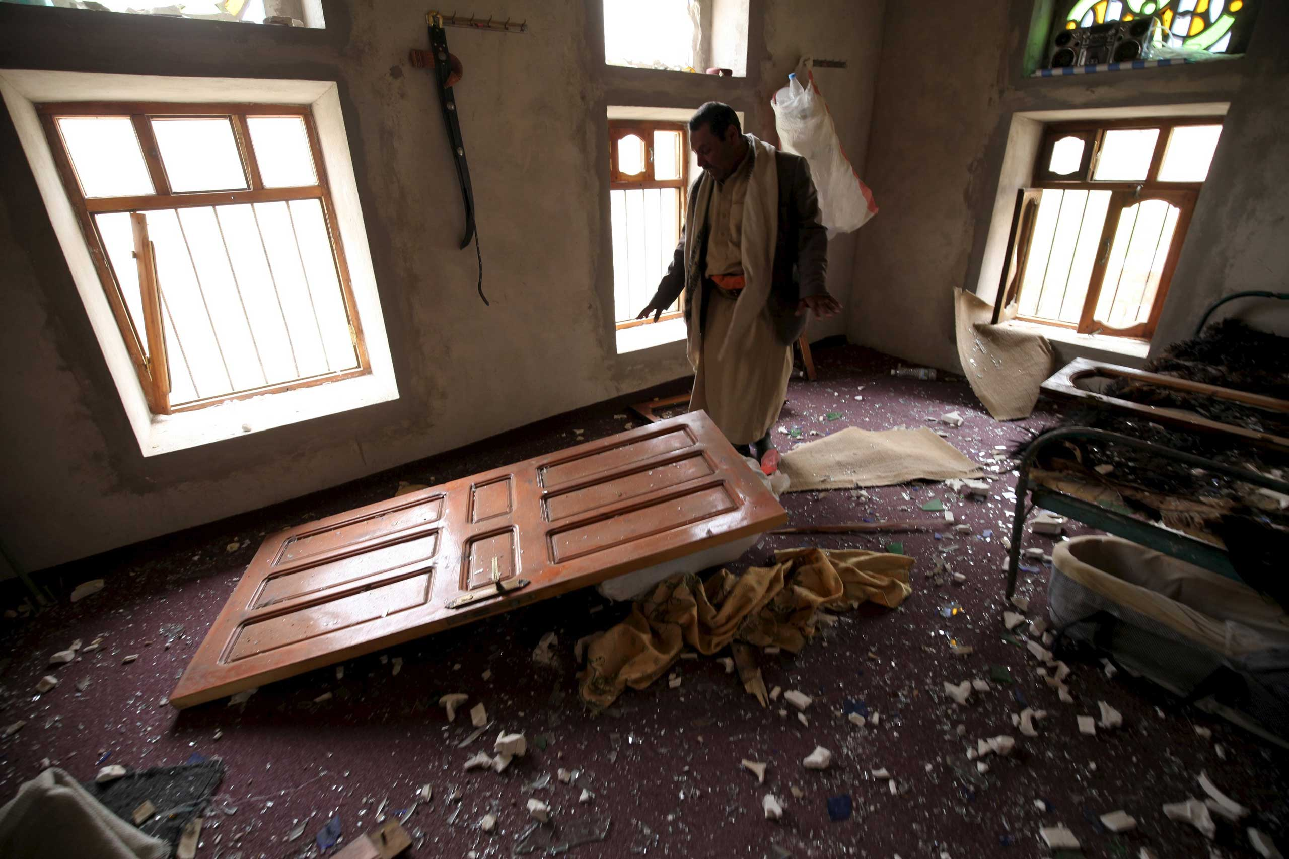 A man shows the damage inside his house after an air strike in the Okash village near Sanaa, Yemen on April 4, 2015.
