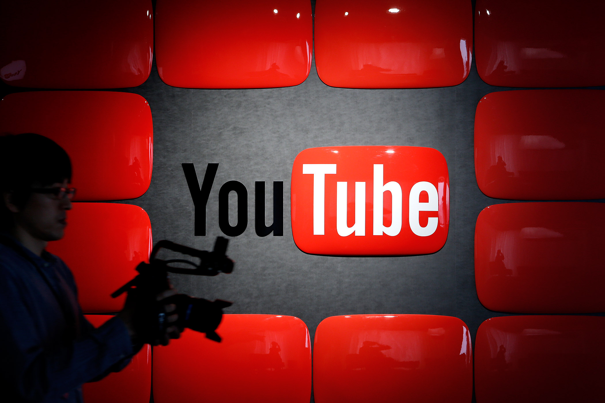 An employee holding recording equipment walks past Google Inc.'s YouTube logo displayed at the company's YouTube Space studio in Tokyo, Japan, on March 30, 2013.