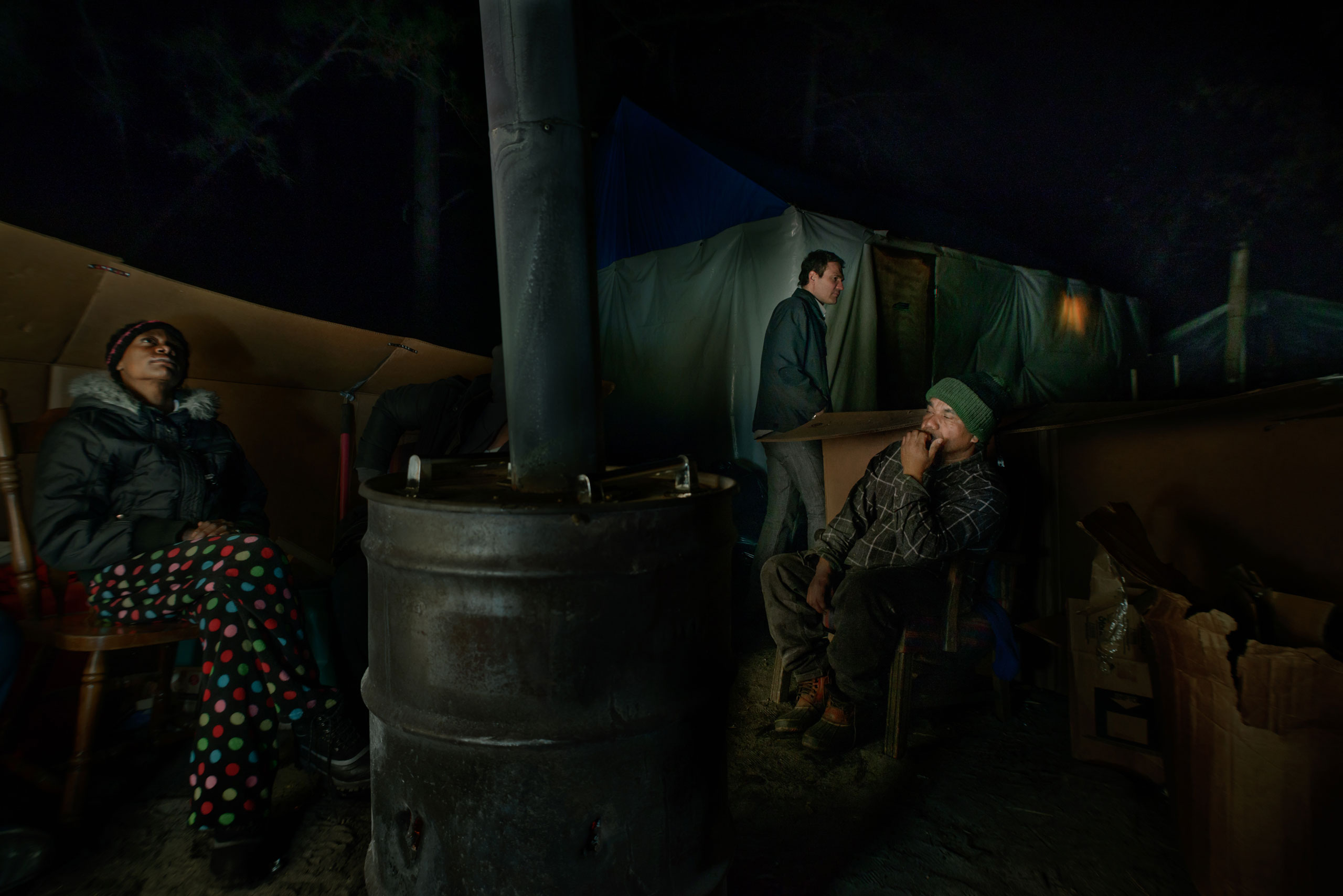 Rev. Steve Brigham, the self-appointed spokesperson for Tent City, heads to the chapel while Eve and Arek star gaze around the fire, March 8, 2014.