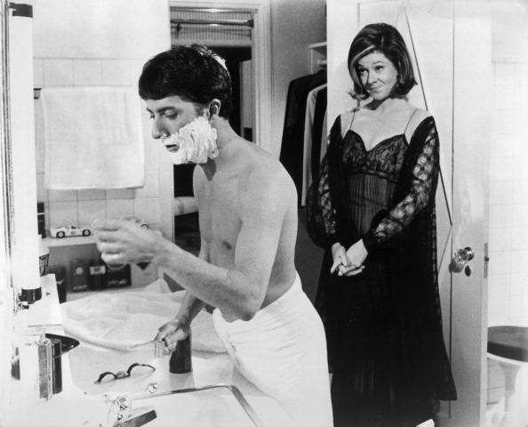 Dustin Hoffman shaves while Elizabeth Wilson stands behind him in a scene from the film The Graduate in 1967