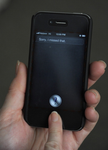 A woman is using  Siri  software on an iPhone.