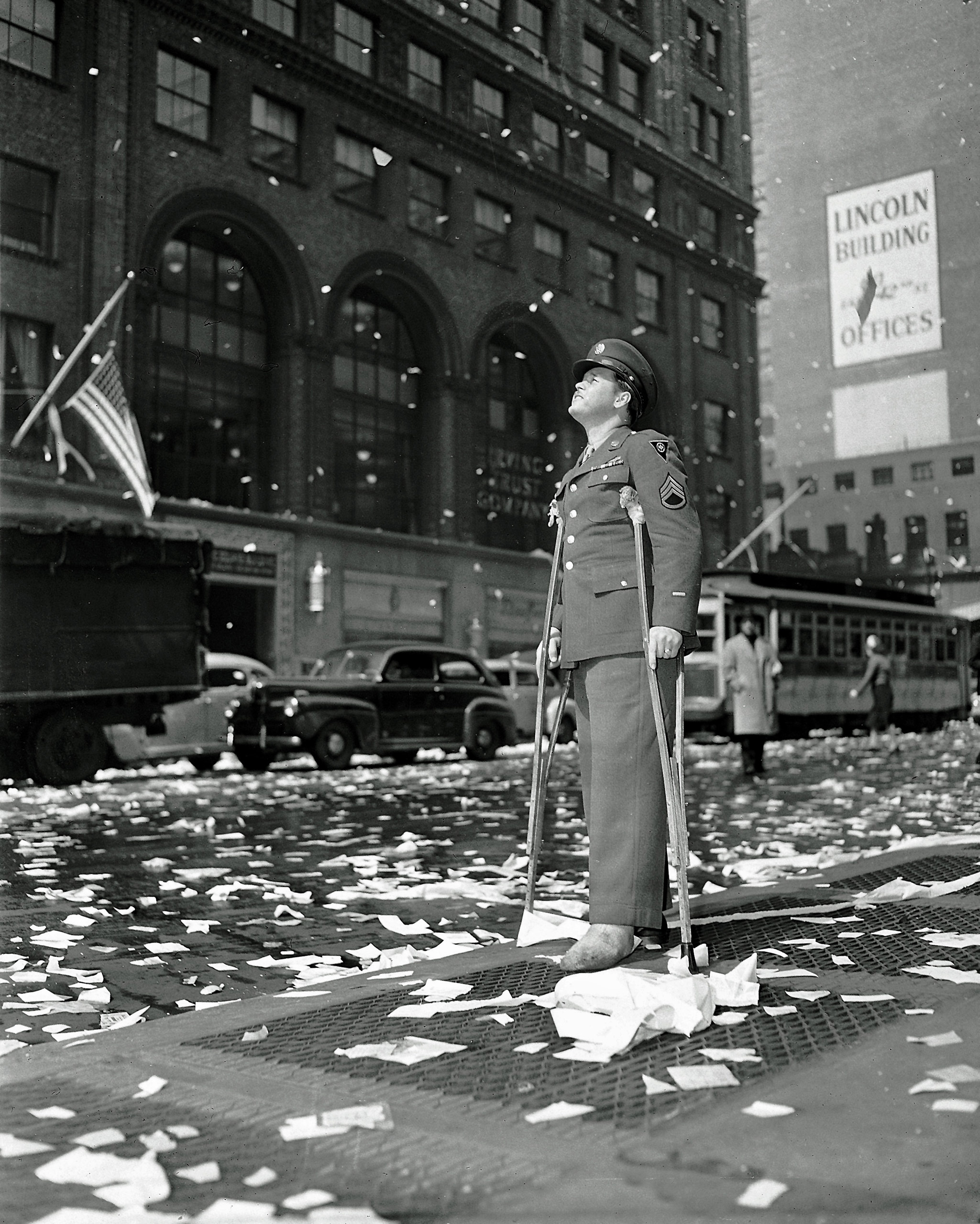 Staff Sgt. Arthur Moore of Buffalo, N.Y., who was wounded in Belgium, stands on 42nd Street near Grand Central Station in New York Monday, May 7, 1945 as New Yorkers celebrate news of VE Day, victory over Nazi Germany.