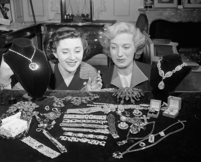 "Jill Ciraldo and Grace Flynt are admiring the McLean Jewel Collection at the establishment of Harry Winston, Inc., international jewer dealer, of New York. The Hope Diamond is at left above and the ""Star of the East"" at right, 1949."
