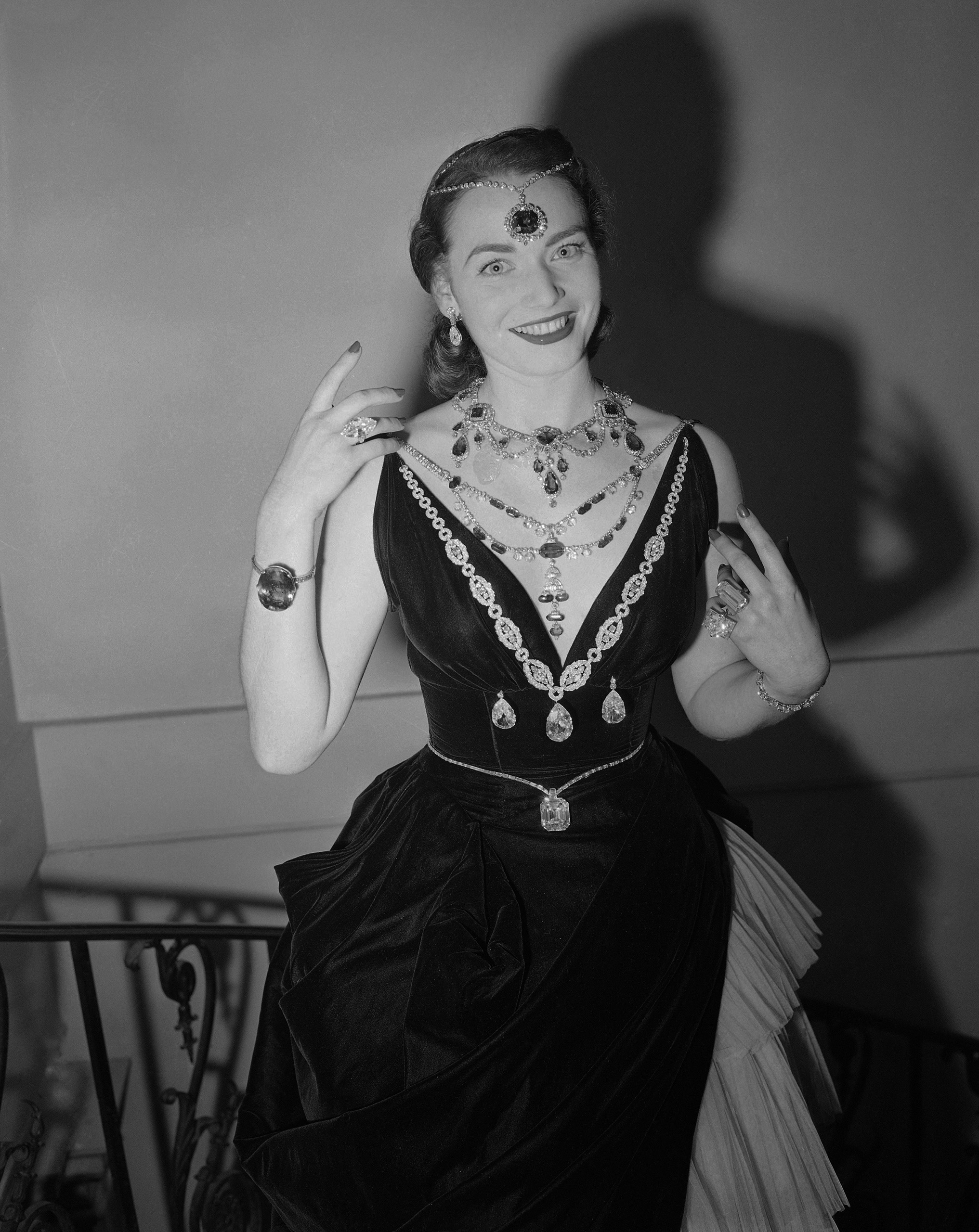 Model Mara Byron displays jewels valued at $ 10,000,000 at a preview of a United Hospital Fund art project exhibition in New York,  November 17, 1949. On her forehead is the Hope Diamond, 44 carats.  Pear-shaped diamond earrings are 30 carats each.    Necklaces from top to bottom are Earl of Dudley emeralds, the Spanish Inquisition period emerald and diamond necklace and, attached to a diamond necklace, the 100-carat Star of the East Diamond. Flanking the latter are two pear shaped largest perfectly matched twin diamonds, in the world, totaling 100 carats.   Below the Star of the East is the 126-carat Jonker Diamond.   On the right arm is the largest sapphire in the world, 337 carats.   On third finger right hand is the marquise ring, over 40 carats.    On left arm is 100-carat diamond bracelet made of diamonds from the Gary estate.  On the third finger left hand is 60-carat Mabel Boll ring.  On small finger is the 35-carat McLean ring.