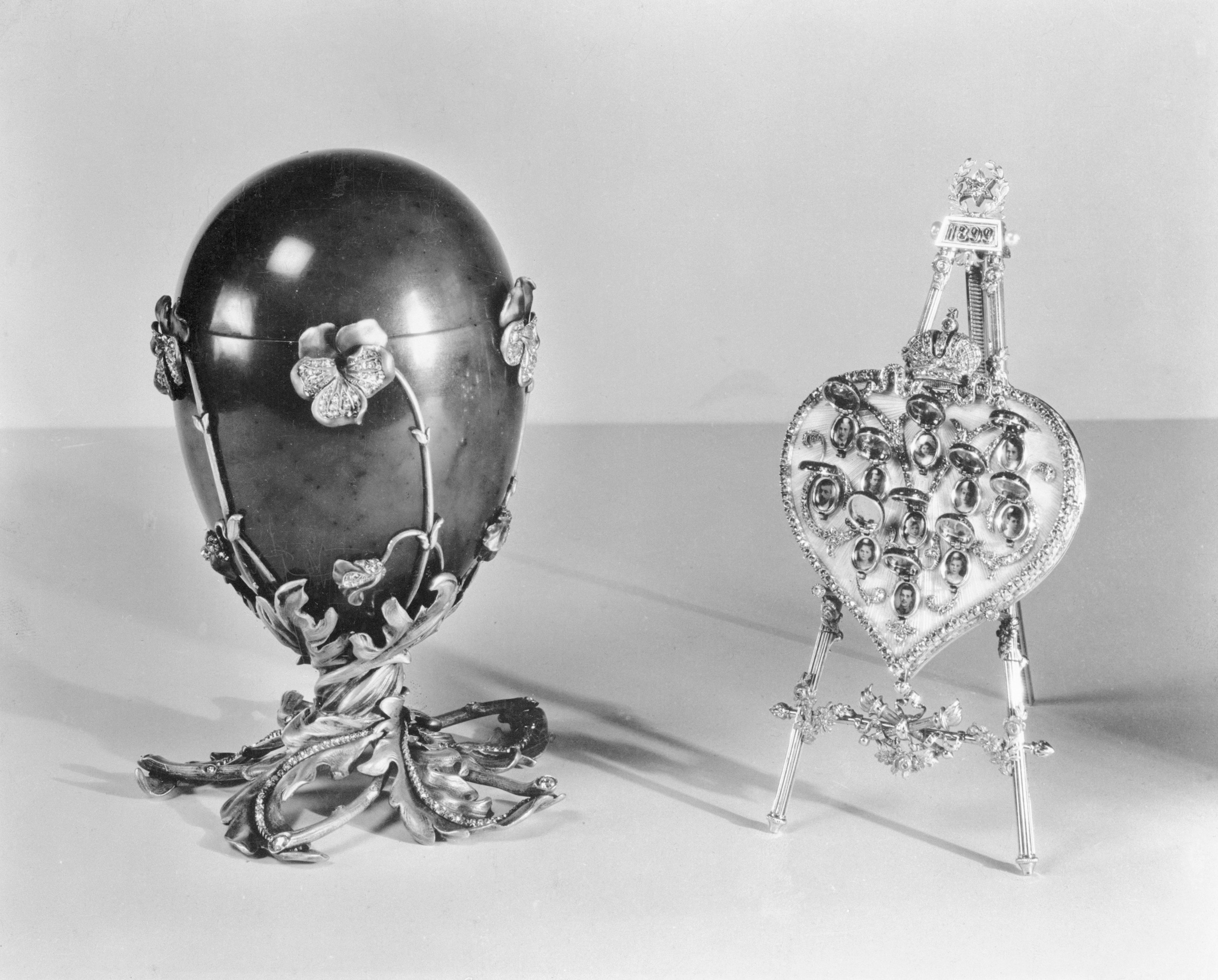 Russian Imperial Gems shown In New York City at the Hammer Galleries in 1937. Spinach jade Fabergé Easter egg, decorated with pansies of enamel and diamonds, mounted on a pedestal of twisted gold leaves and twigs, also studded with diamonds. It contains a folding easel in the shape of a diamond-studded heart, covered with translucent enamel. The heart is surmounted by the Imperial Crown in diamonds. It was presented by Czar Nicholas II to his mother, the Dowager Empress Marie, at Easter in 1899.