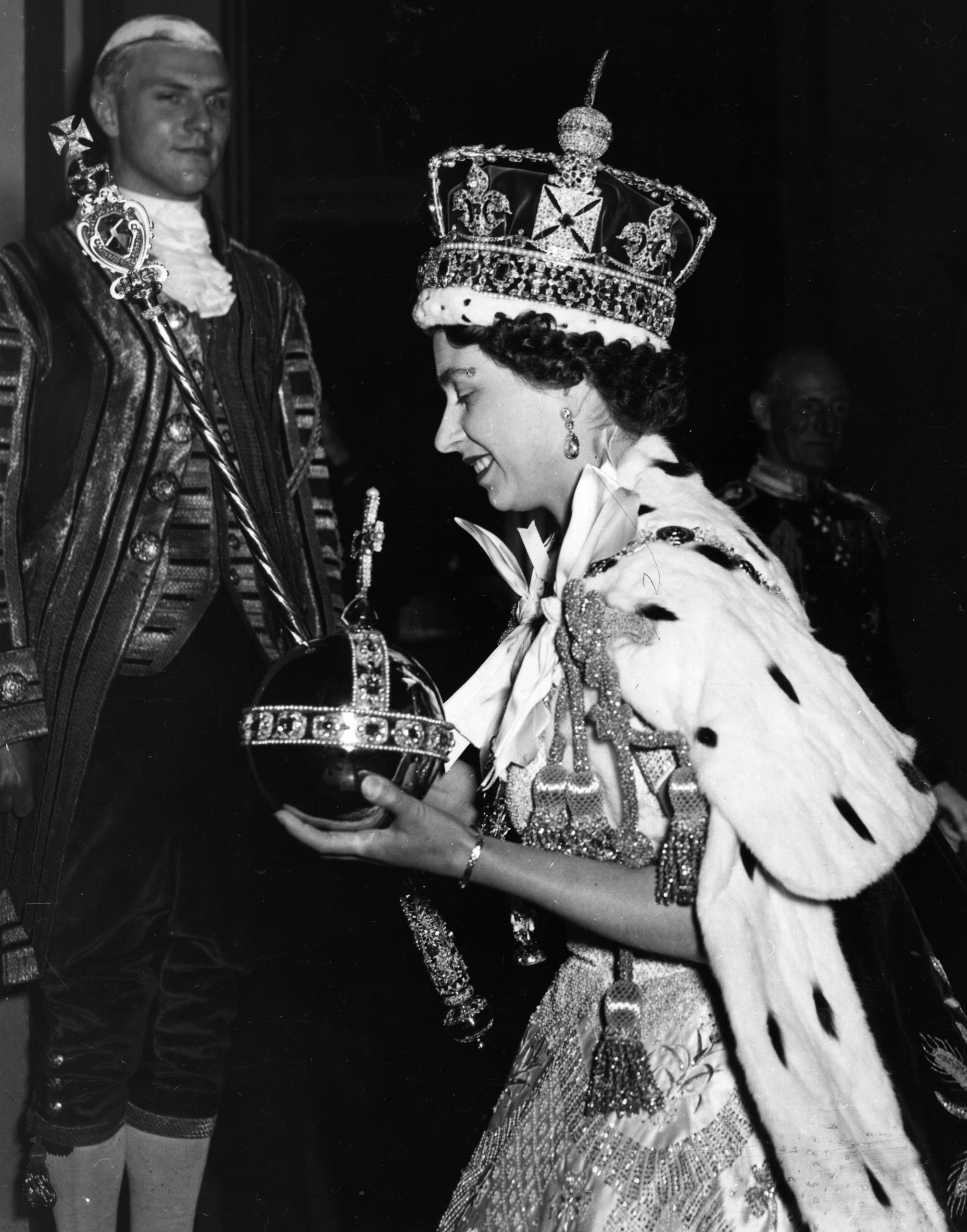 Queen Elizabeth II wearing the Imperial state Crown and carrying the Orb and sceptre, leaving the state coach and entering Buckingham Palace, after the coronation on June 2, 1953.