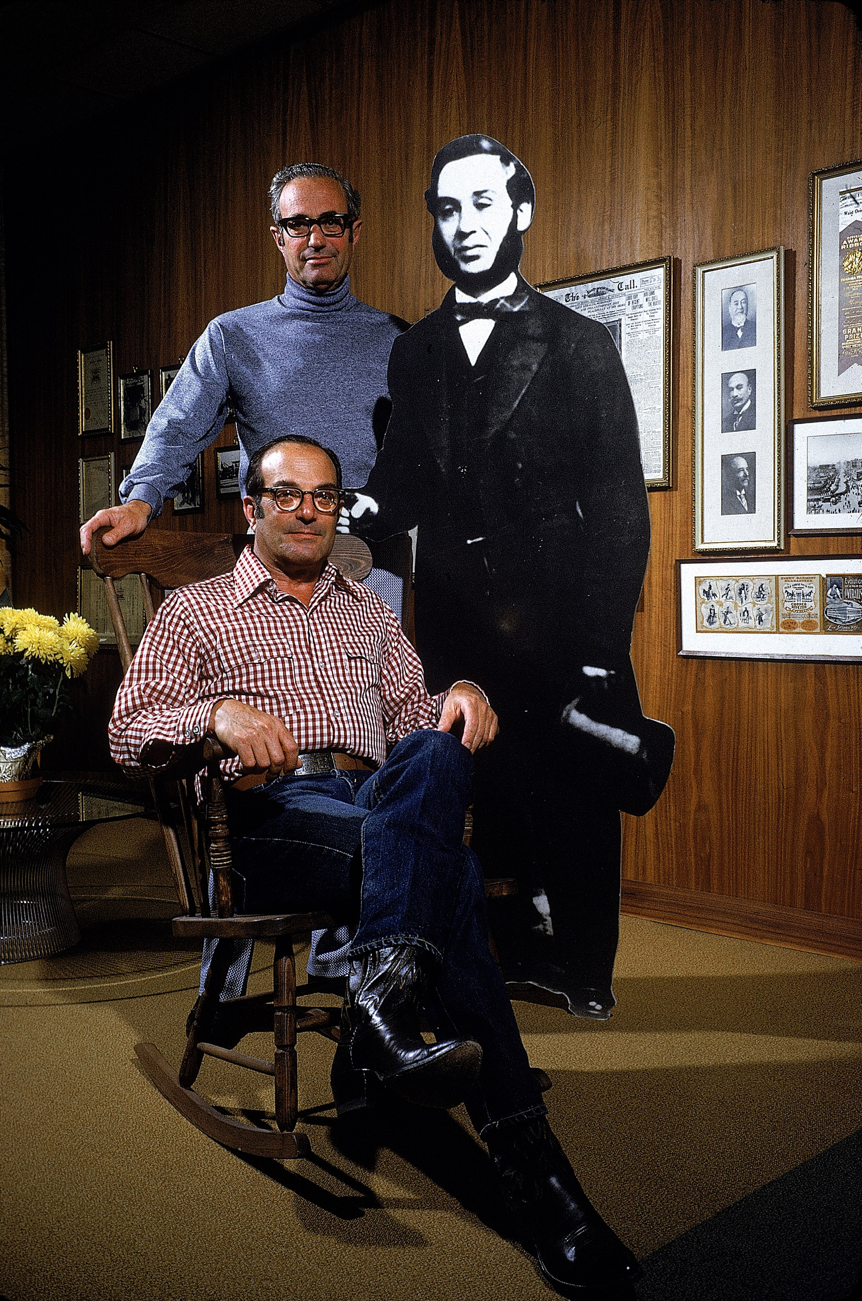 Peter Haas, President of Levi Strauss (seated) and former company president, his brother Walter (standing), next to cut-out of company founder, 1972.