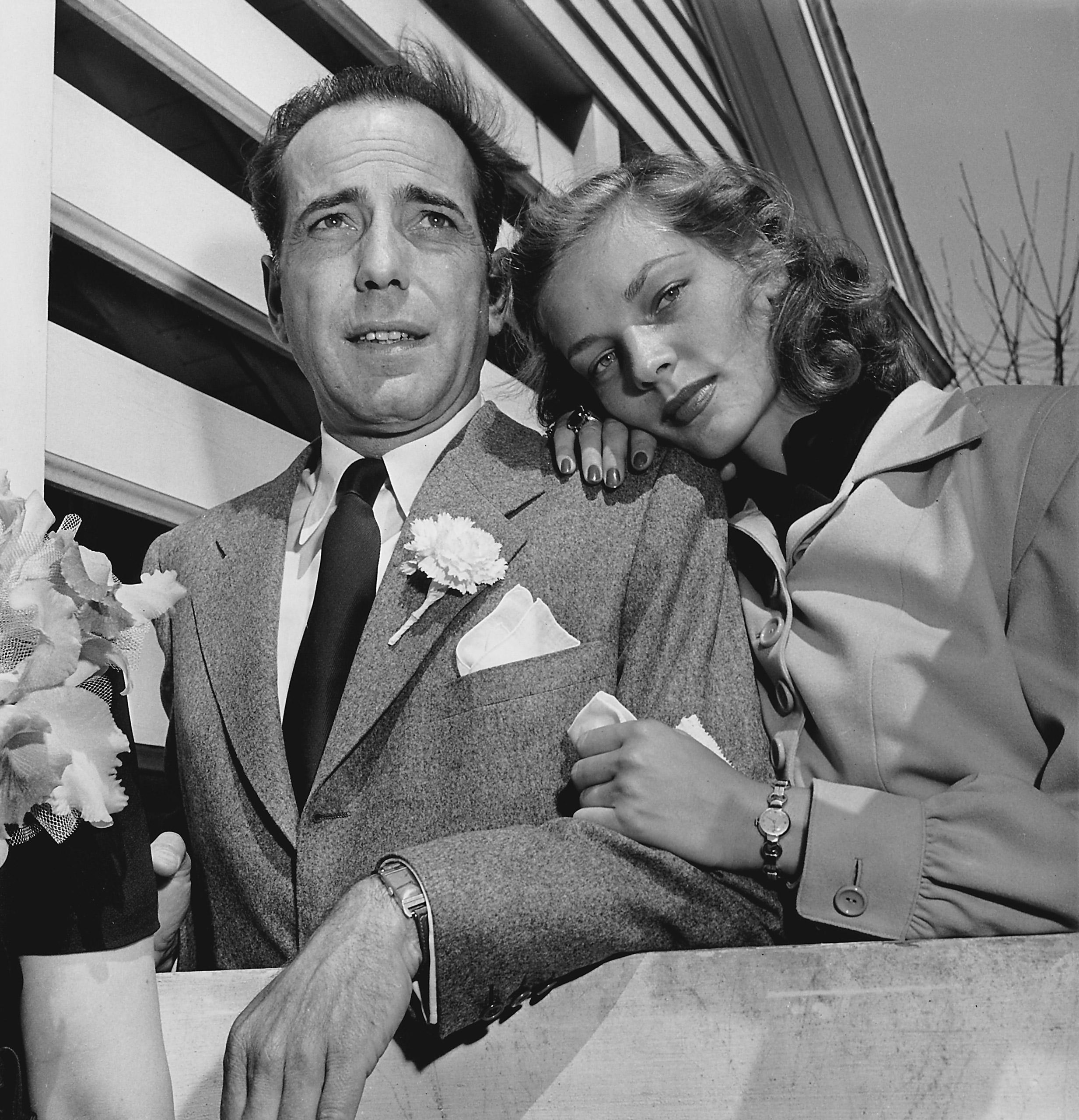Newlywed actors Humphrey Bogart and Lauren Bacall attending wedding reception at the home of novelist Louis Bromfield.