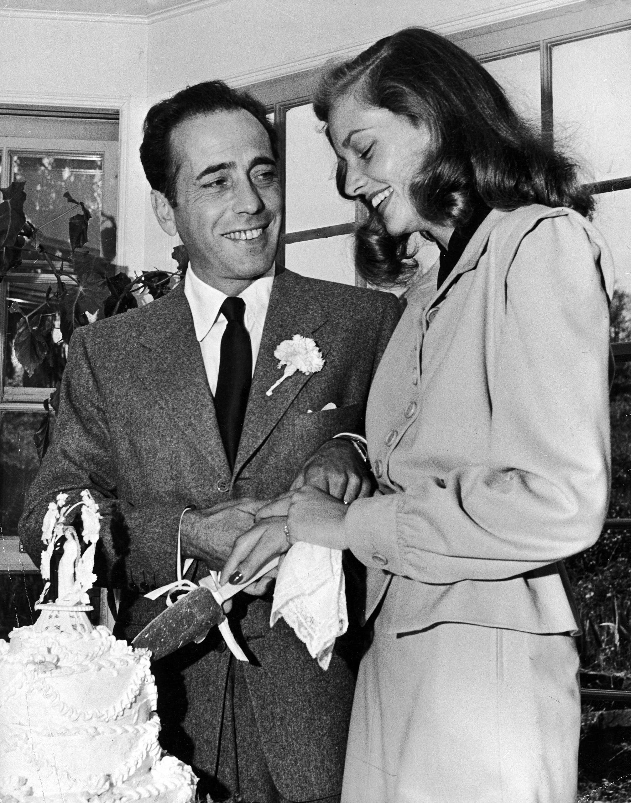 Bogart and Bacall cut the wedding cake.