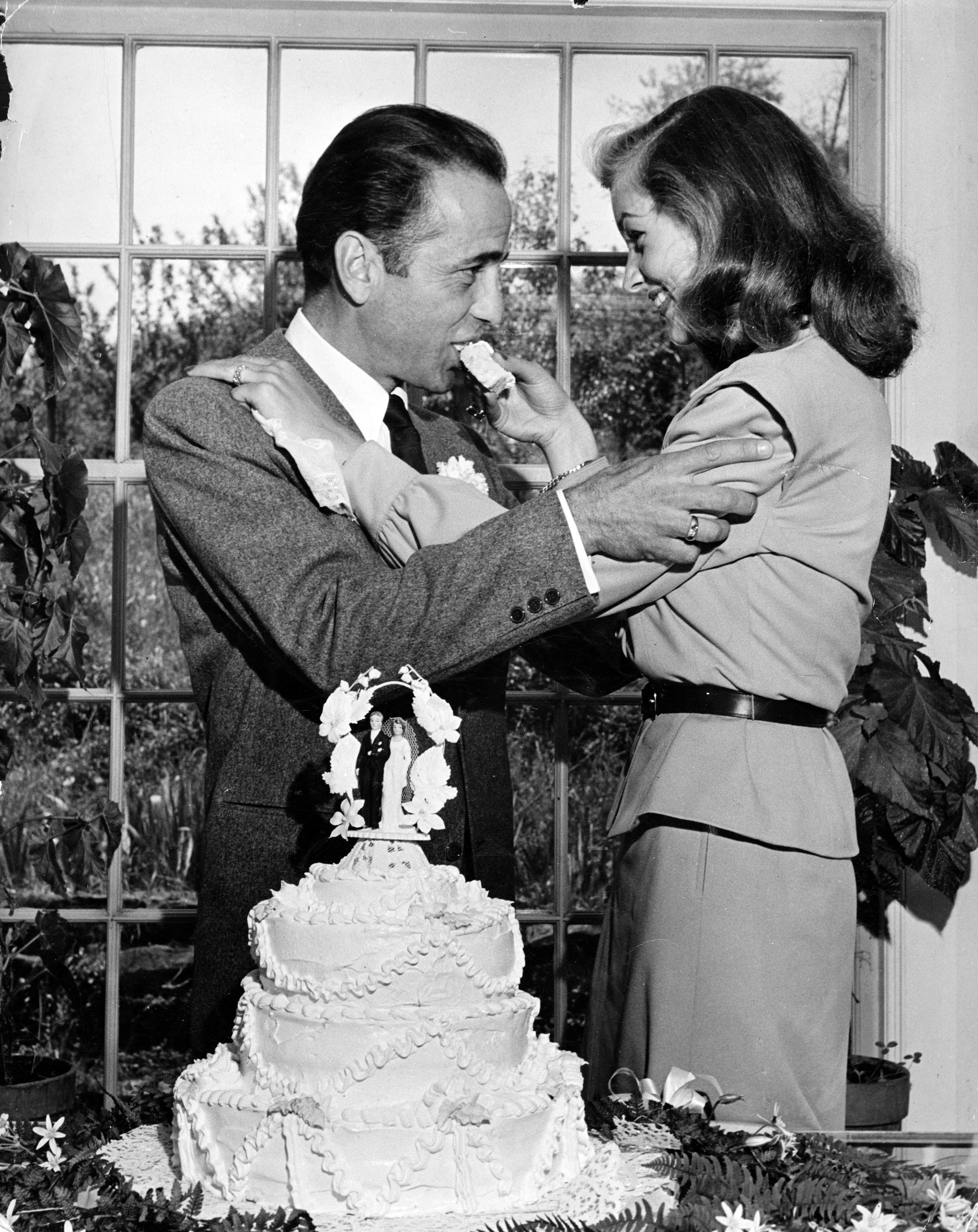 <b>Caption from LIFE.</b> Lauren Bacall feeds wedding cake to her tough-guy groom, Humphrey Bogart, after their marriage ceremony in Ohio.