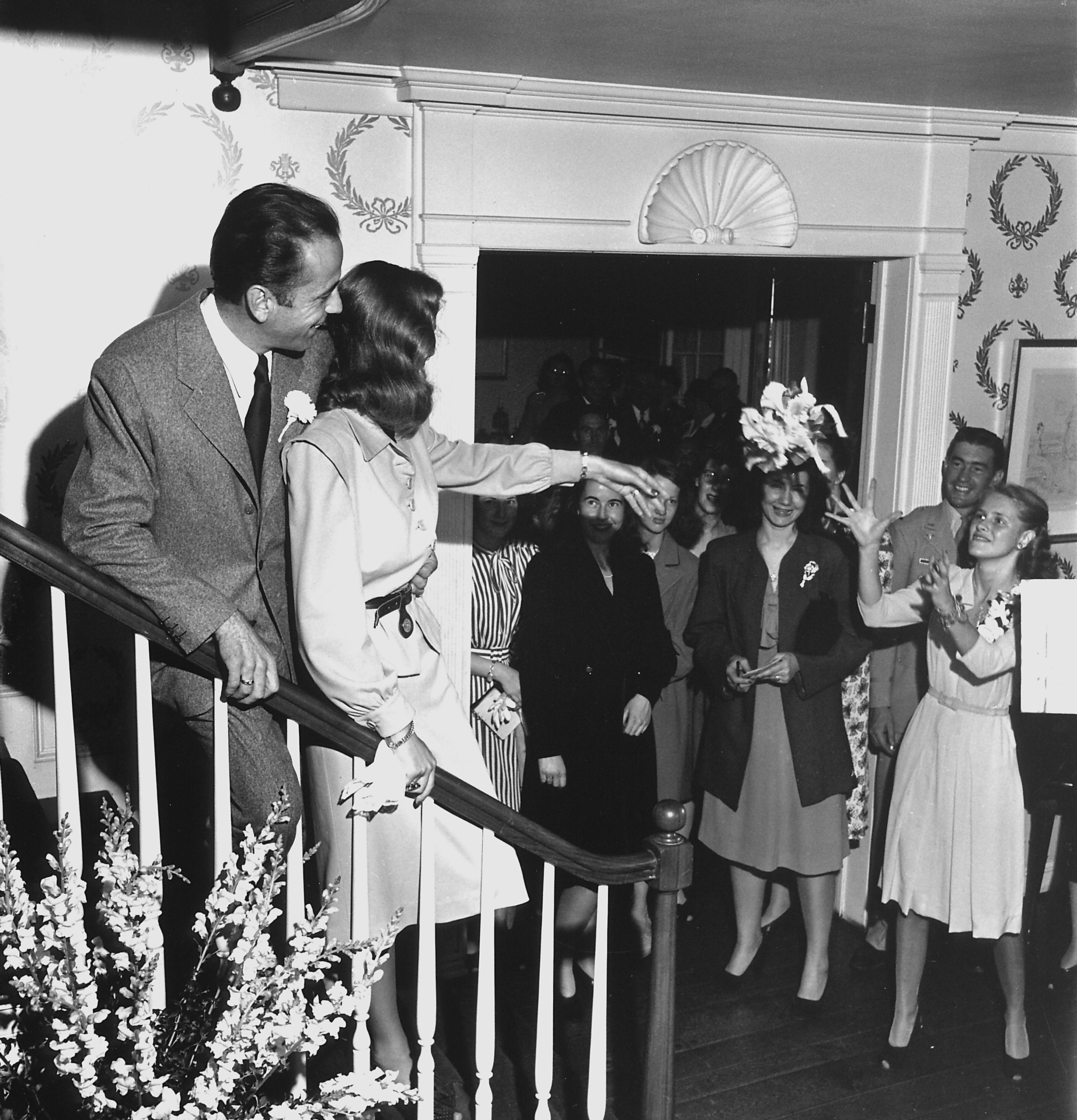 Bacall tosses her bouquet to an eager crowd.