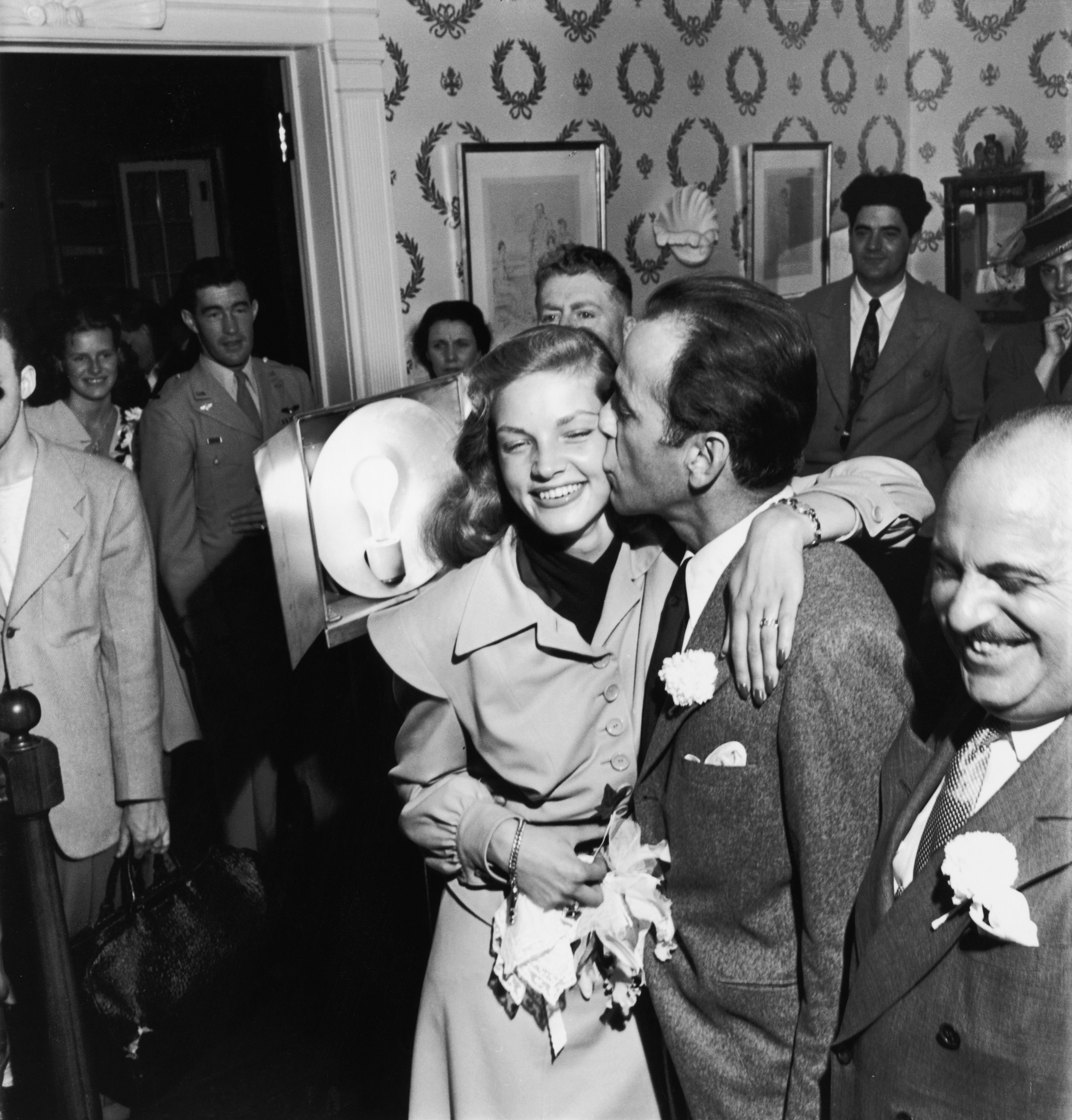 Bogart gives his bride a kiss on the cheek.