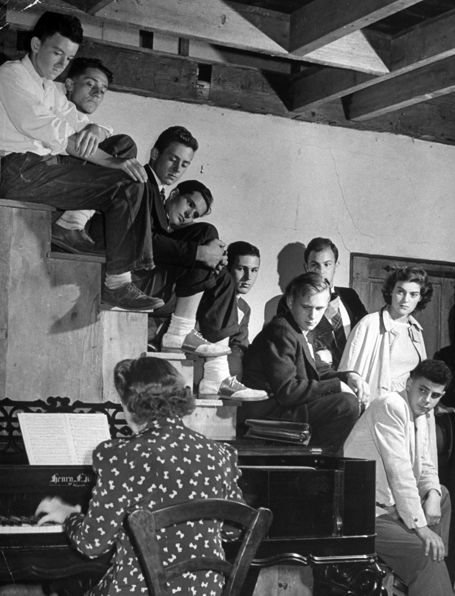 <b>Caption from LIFE.</b> Sober young audience for the music of skillful Ania Dorfmann, concert pianist, includes these Land Corps boys and girls, in the studio of Miss Thompson's home. This part of house was once a barn, built about 1840. The unrailed stairs lead to loft above.