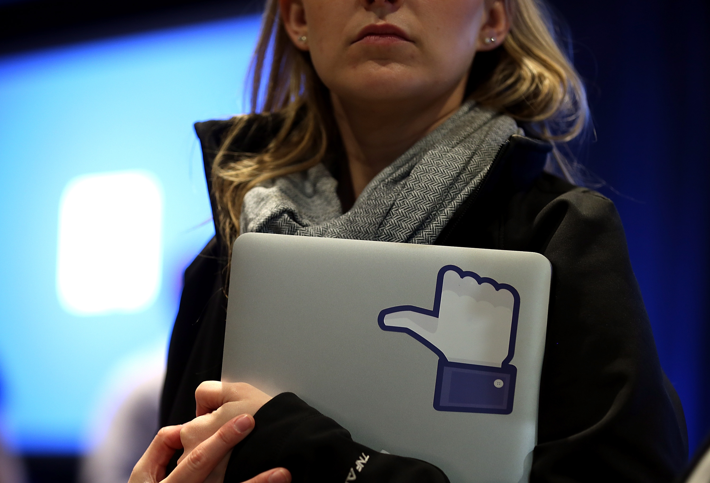 A Facebook employee holds a laptop with a  like  sticker on it during an event at Facebook headquarters during an event at Facebook headquarters on April 4, 2013 in Menlo Park, California.