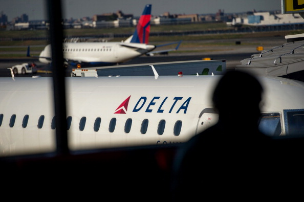The silhouette of a passenger waiting for a flight is seen in the Delta Air Lines Inc. terminal at LaGuardia Airport in New York on Oct. 21, 2013.