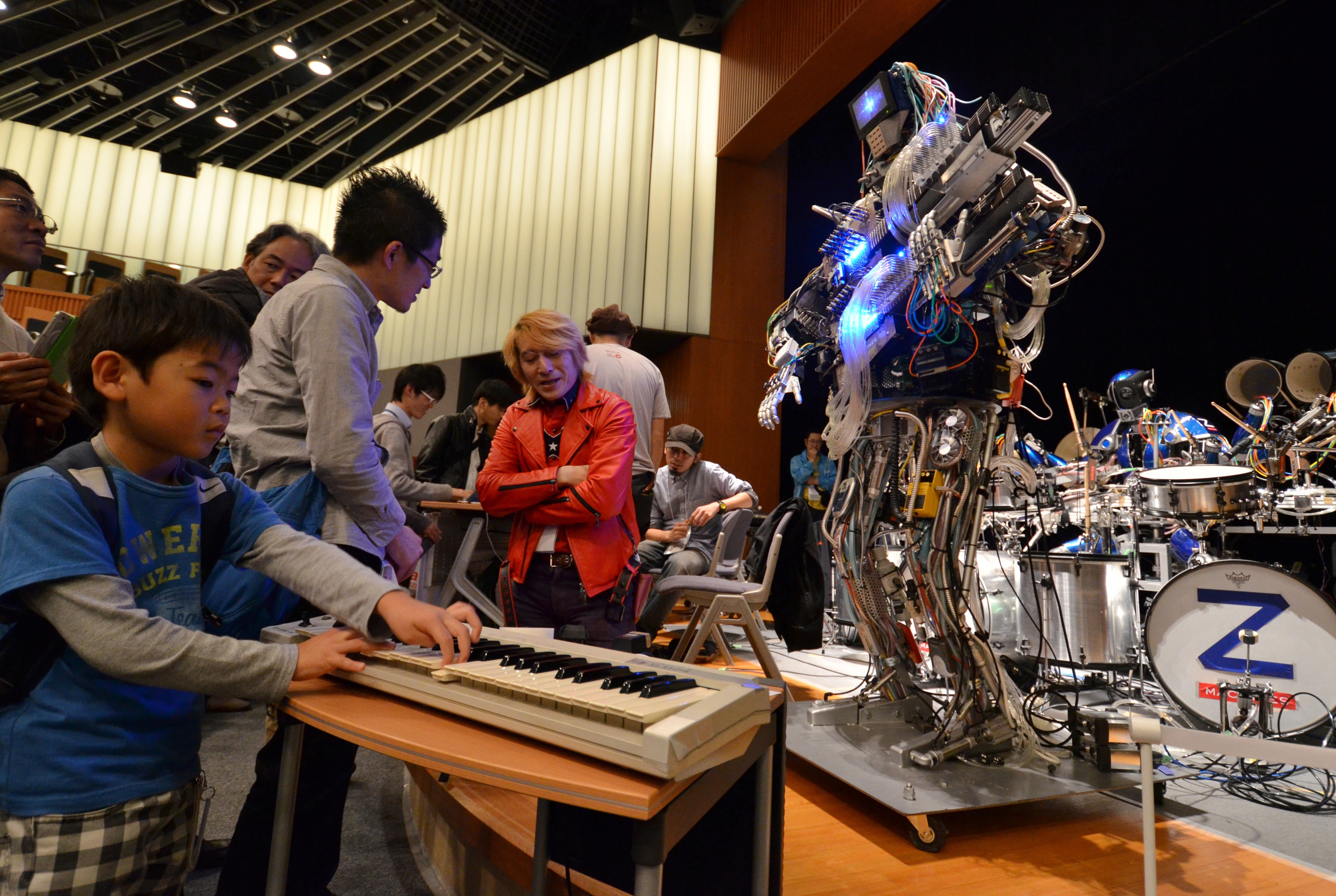 A boy plays a keyboard to control robot guitarist  Mach , a member of a robot rock band  Z-Machines , during the two day art and technology event  Maker Faire Tokyo  at the National Museum of Emerging Science and Innovation in Tokyo on November 3, 2013.