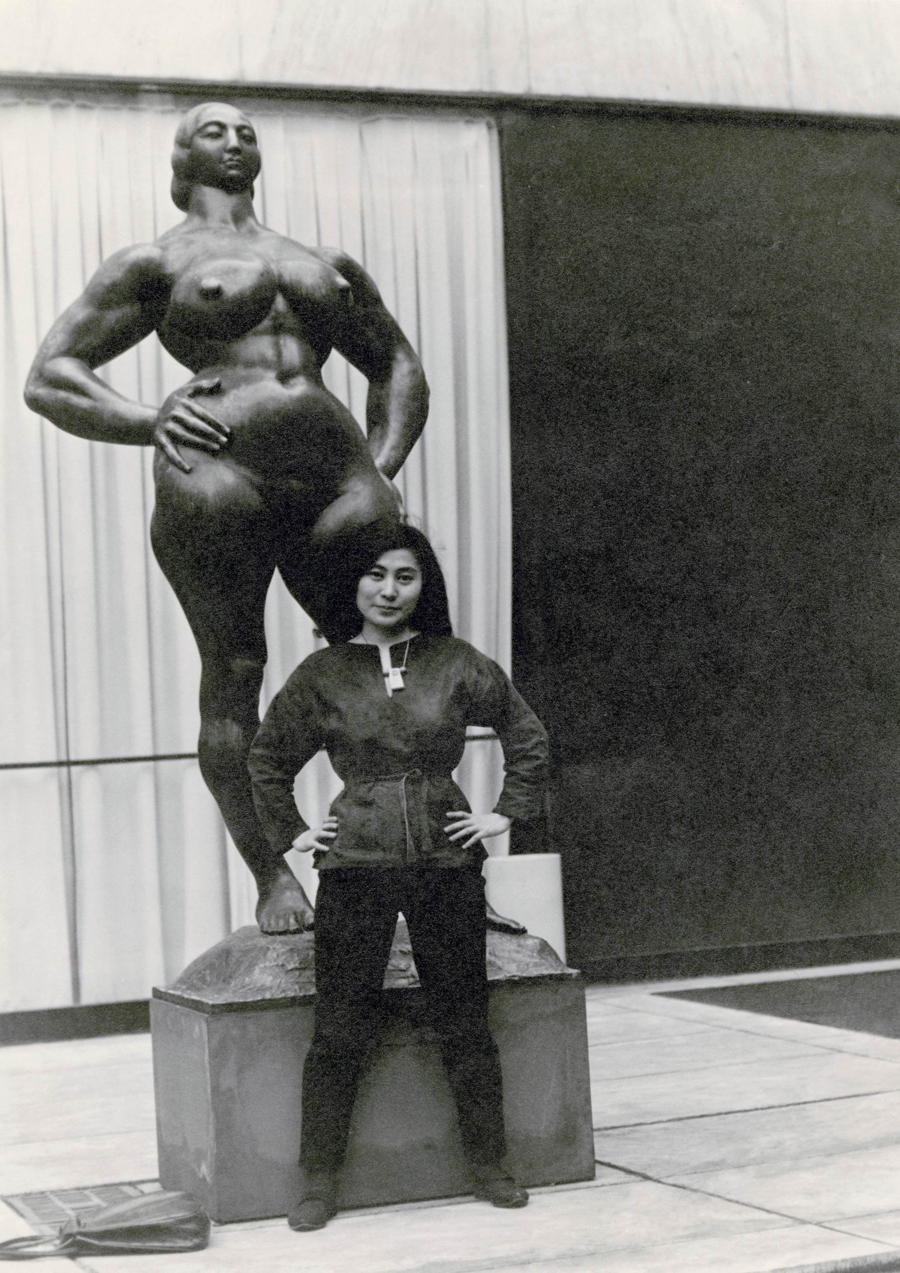 Yoko Ono stands next to <i>Standing Woman</i>, 1932, by Gaston Lachaise at The Museum of Modern Art Sculpture Garden in New York, circa 1960–61.