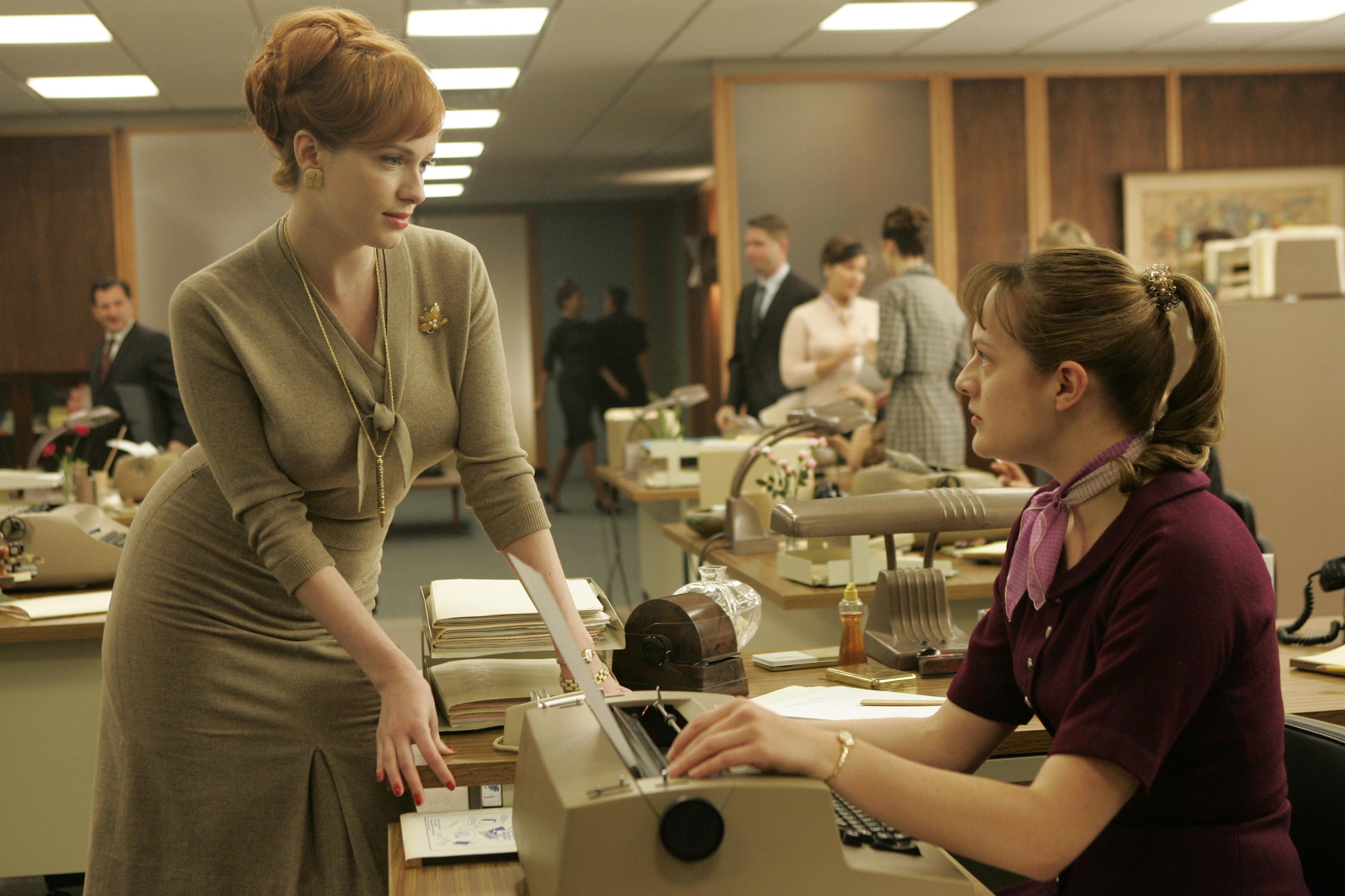 Joan Holloway (Christina Hendricks) and Peggy Olson (Elisabeth Moss) - Mad Men - Season 1, Episode 2 - Photo Credit: Doug Hyun/AMC