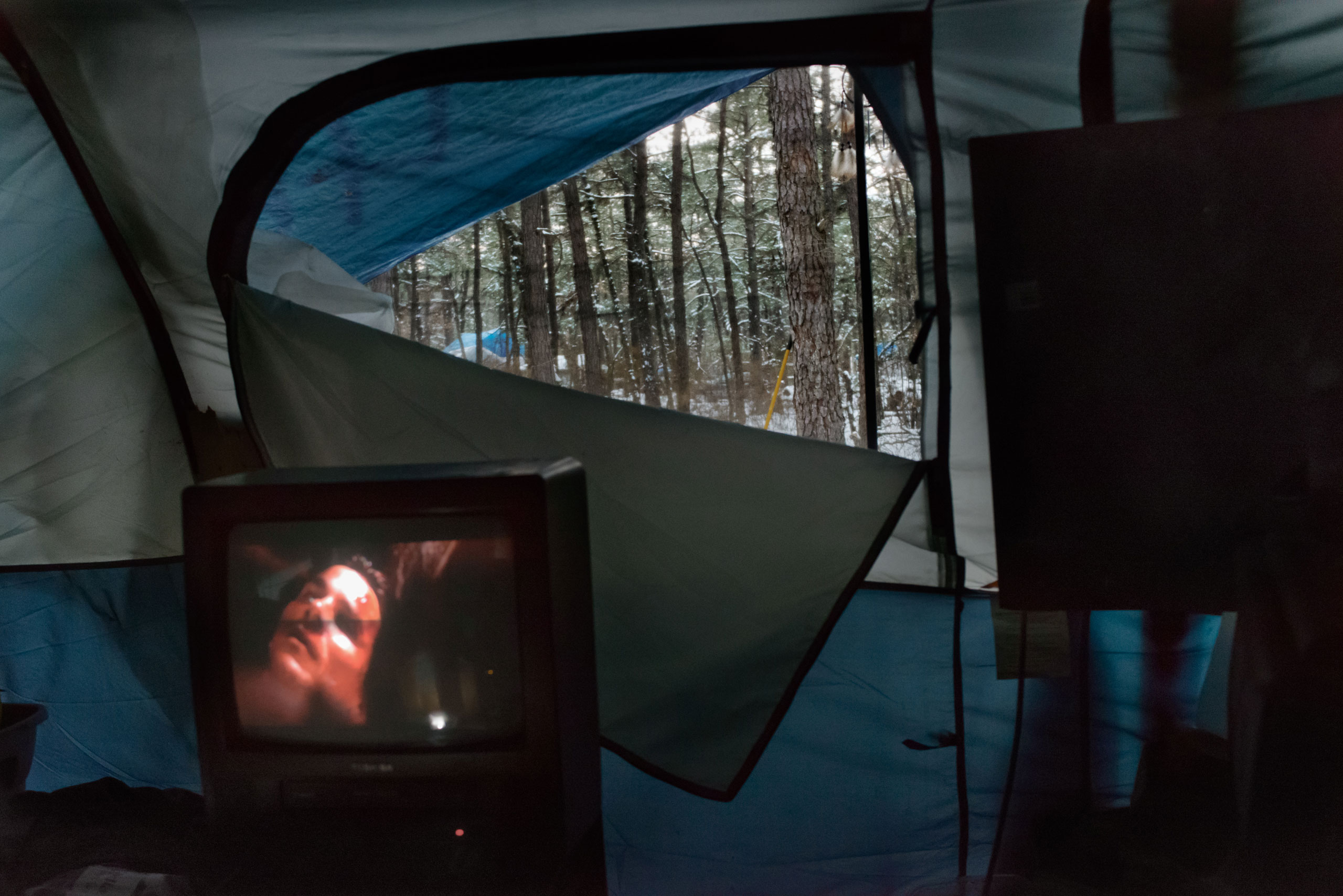 Tent City residents watch the latest batman film on DVD powered by a generator, March 3, 2014.