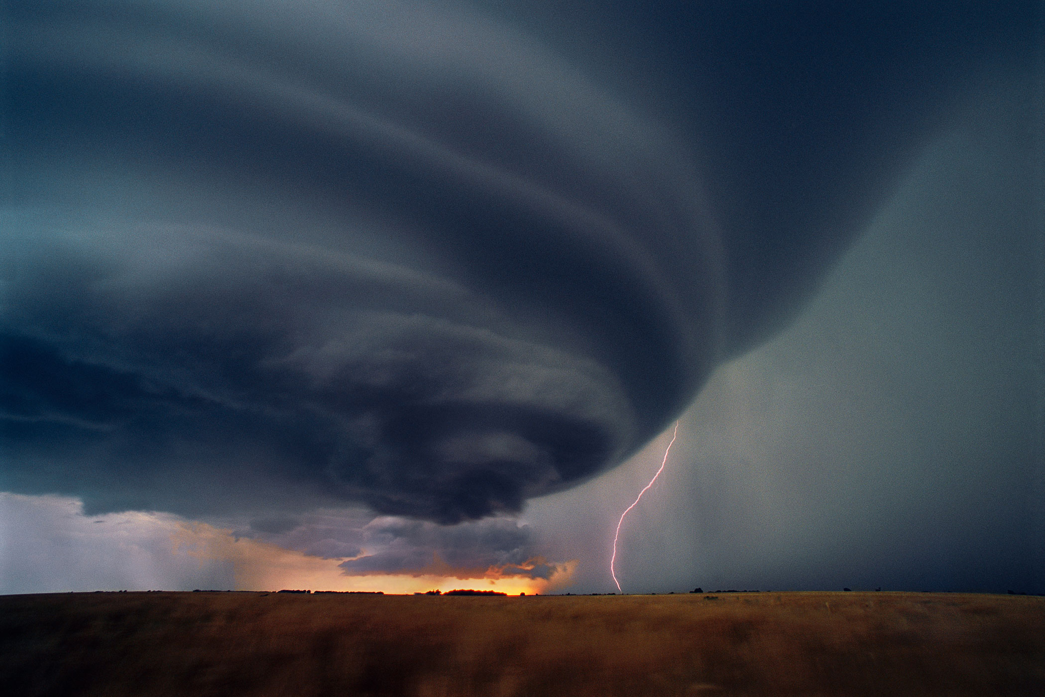 A lone lightning bolt strikes the ground beneath an isolated supercell thunderstorm at sunset in Kansas, June 5, 2004.