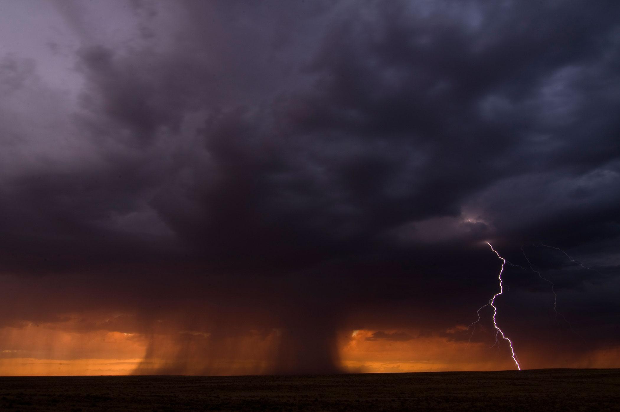 Summer rain storms and lightning roll across the plains near the Petrified Forest National Park, in Navajo, Ariz., Aug. 31, 2011.