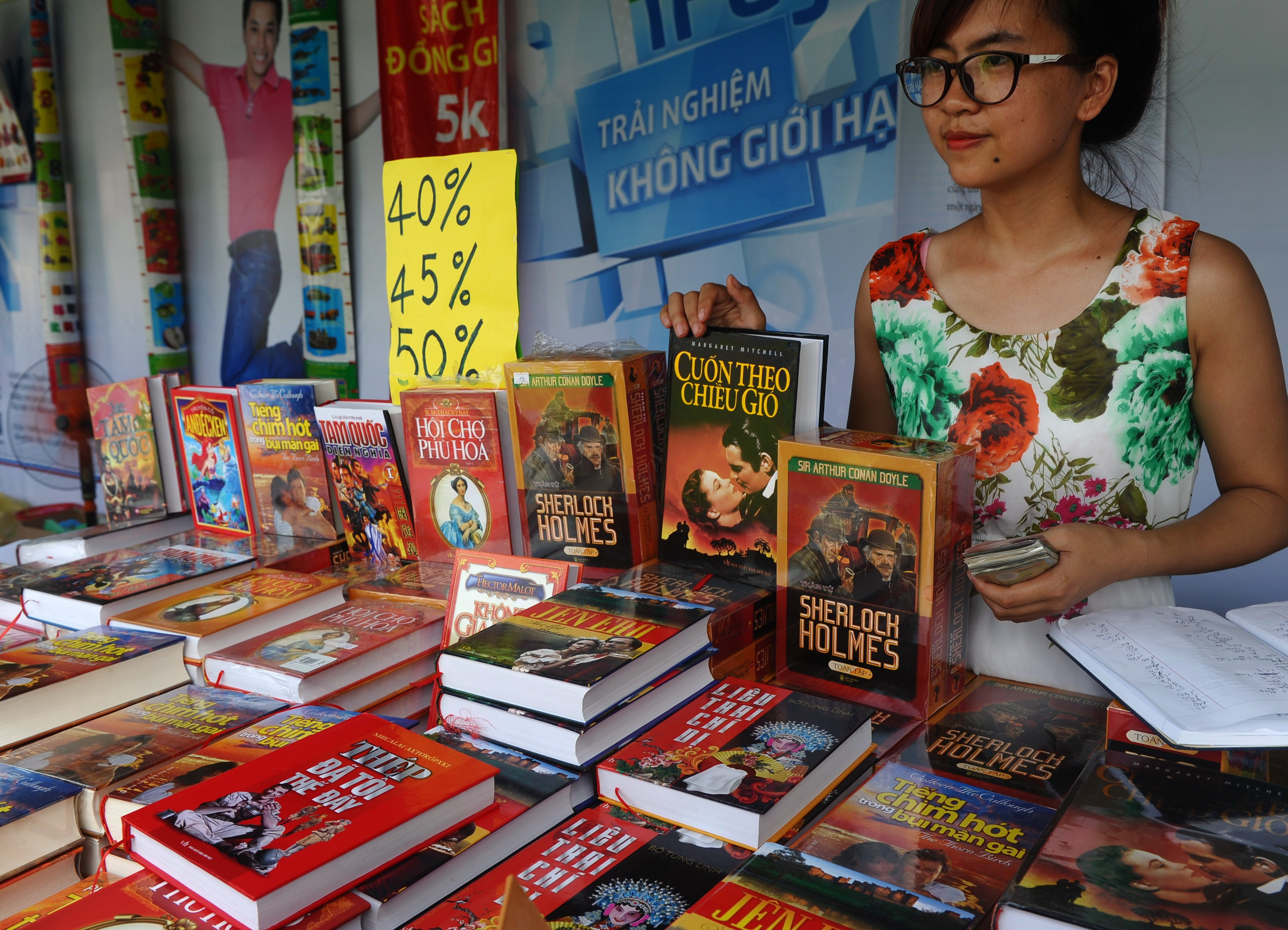A publishing-house employee stands at a booth selling discount foreign novels at a book festival in Hanoi on Sept. 30, 2014