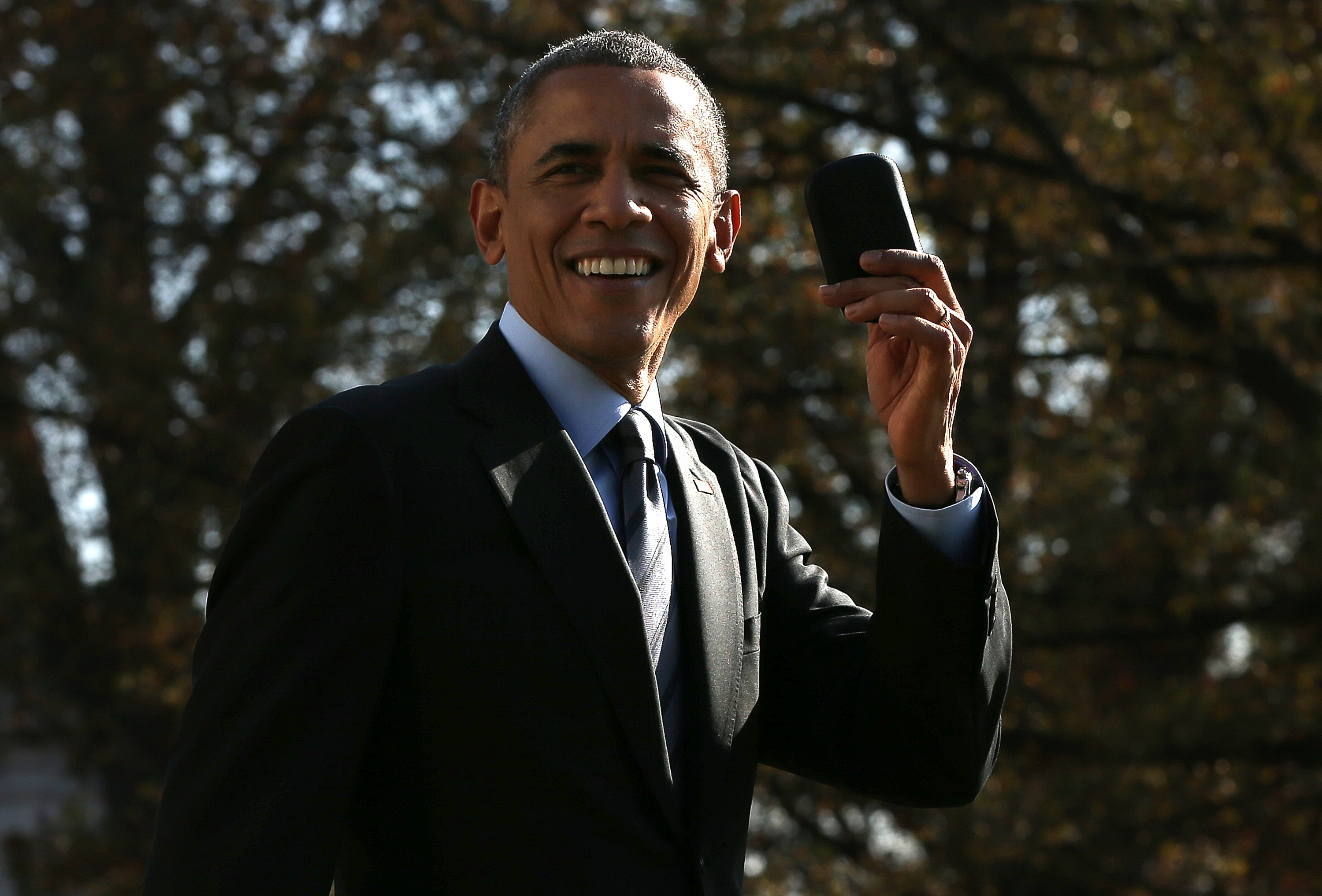 U.S. President Barack Obama holds up his Blackberry after he ran back into the White House after forgetting the mobile phone while departing for a domestic trip November 21, 2014 in Washington, DC.