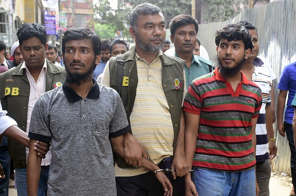 Bangladesh police escort two men accused in the murder of blogger Washiqur Rahman for a court appearance in Dhaka on March 31, 2015