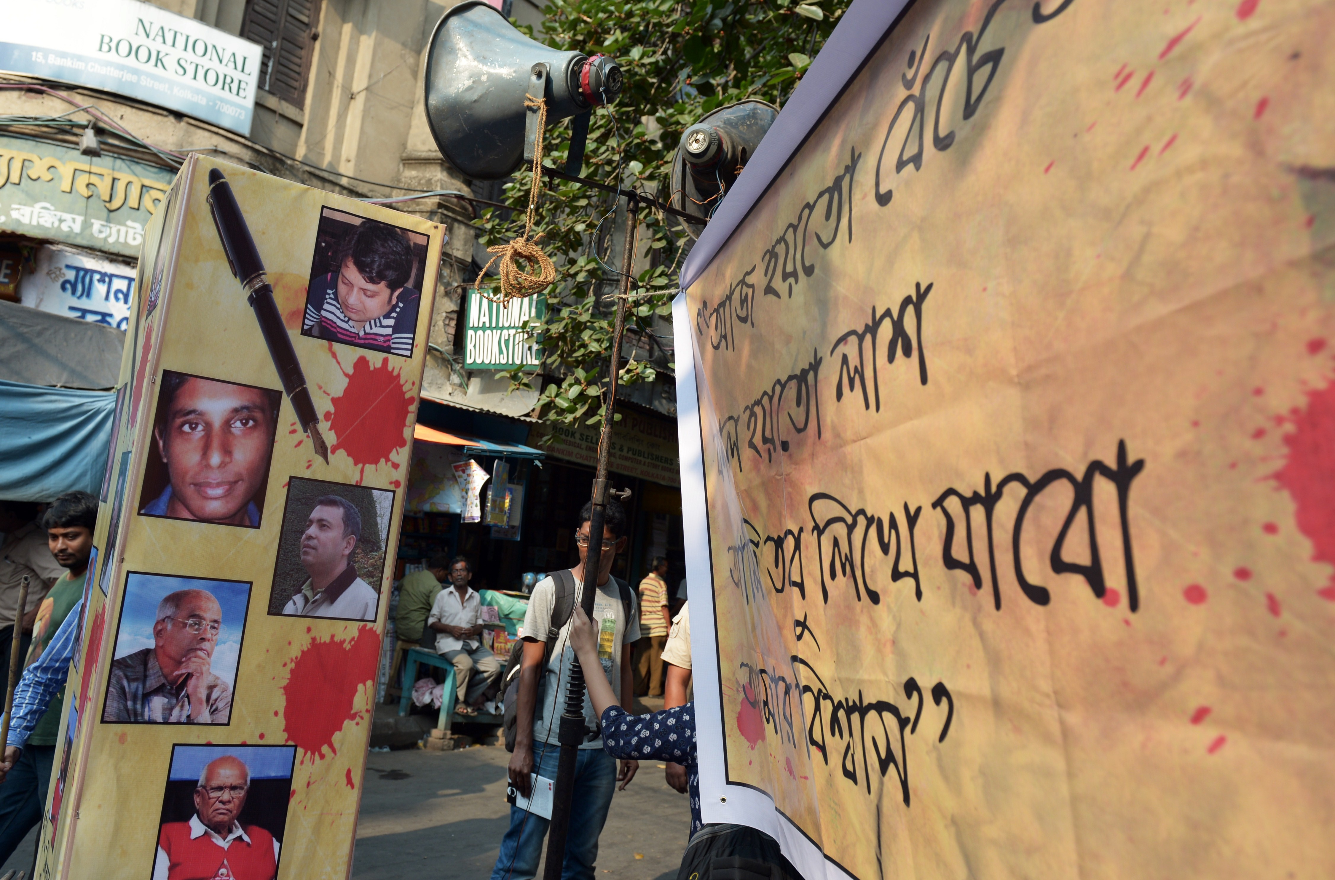 An Indian student looks from behind a poster with pictures of recently killed Bangladeshi bloggers during a protest meeting organized to pay homage in Kolkata on May 16, 2015.
