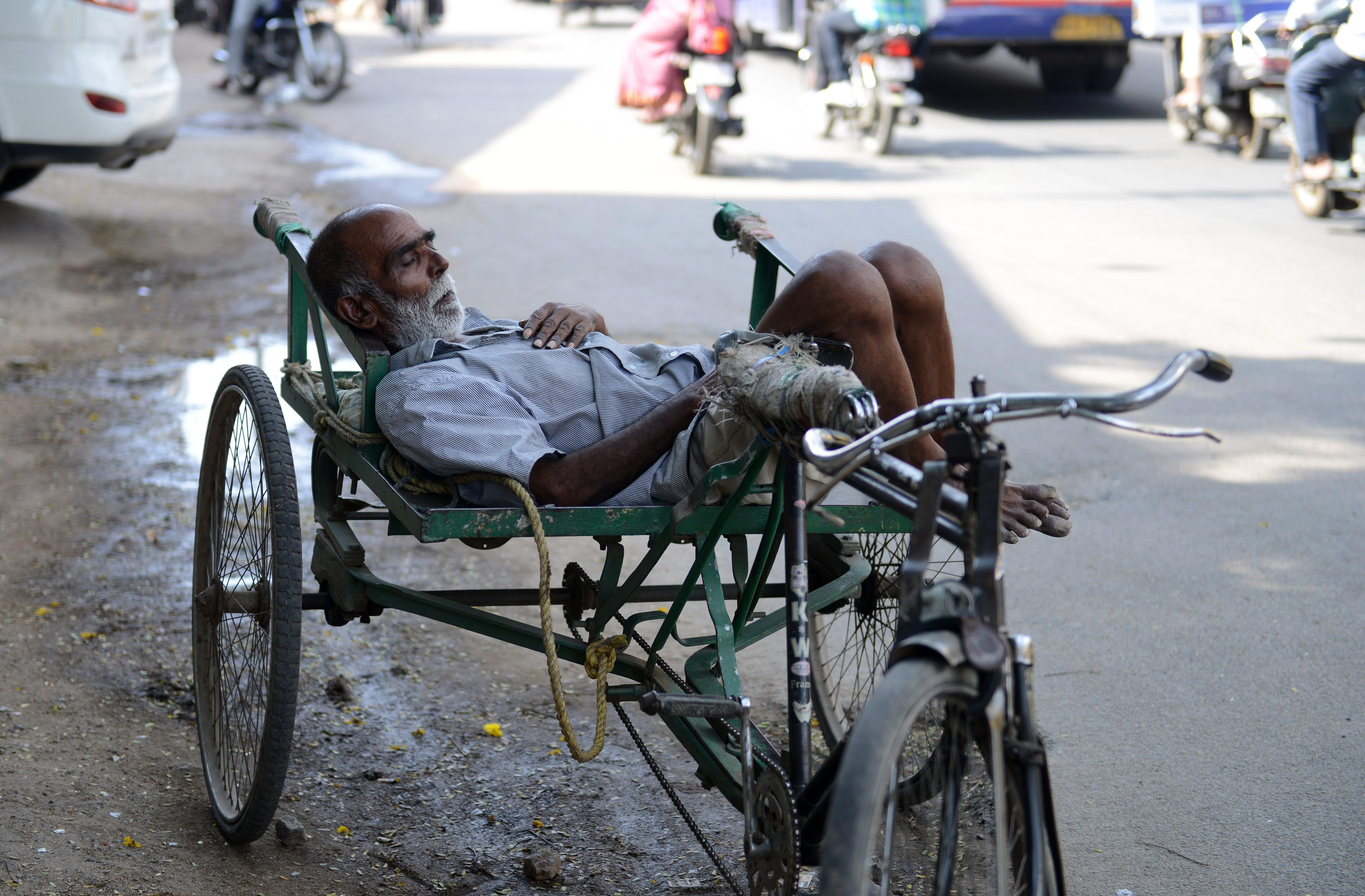 An Indian resident sleeps in the shade on a tricyle at the roadside in Hyderabad on May 22, 2015