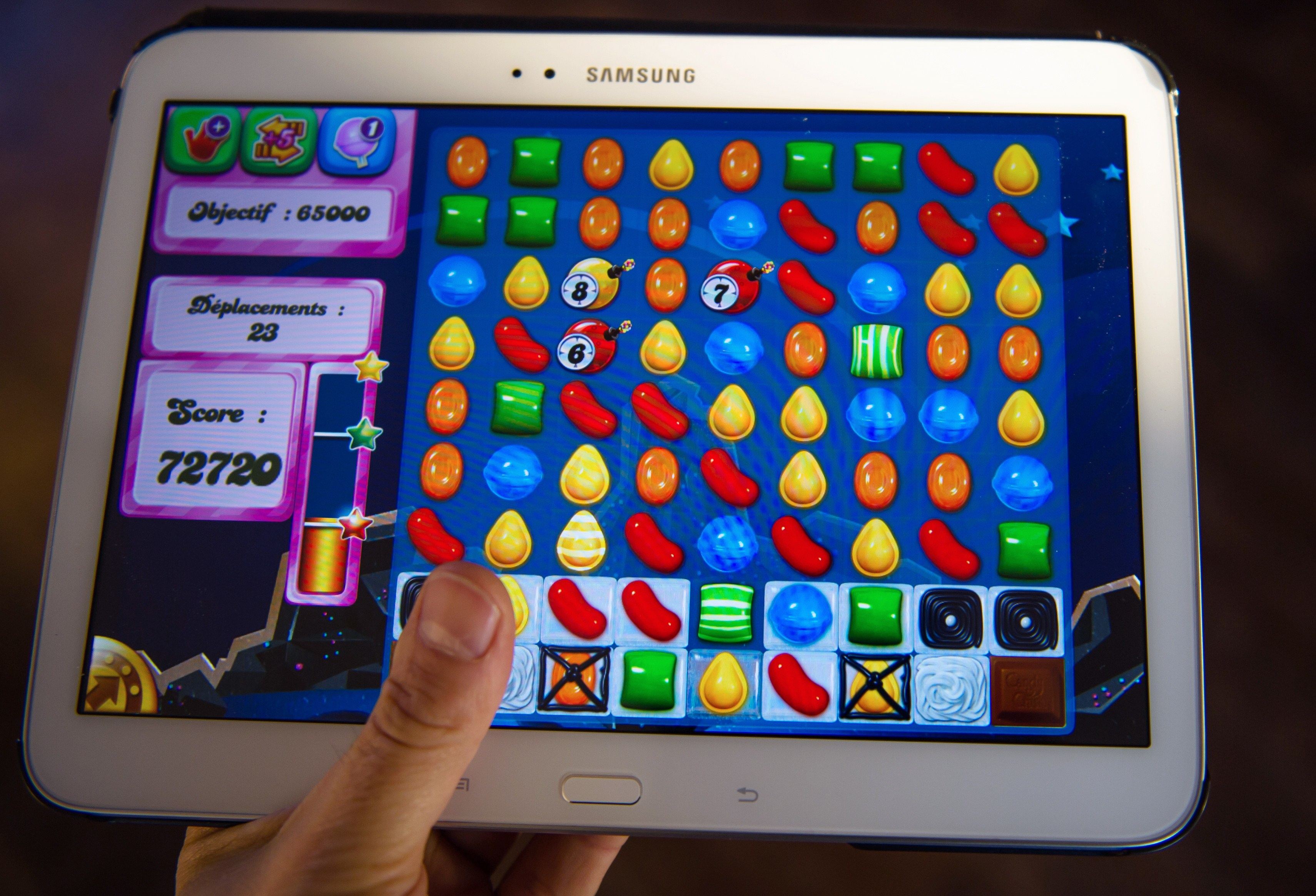 A person plays on his tablet with Candy Crush Saga games developed by British King Digital Entertainment, on March 6, 2014, in Lille, northern France.