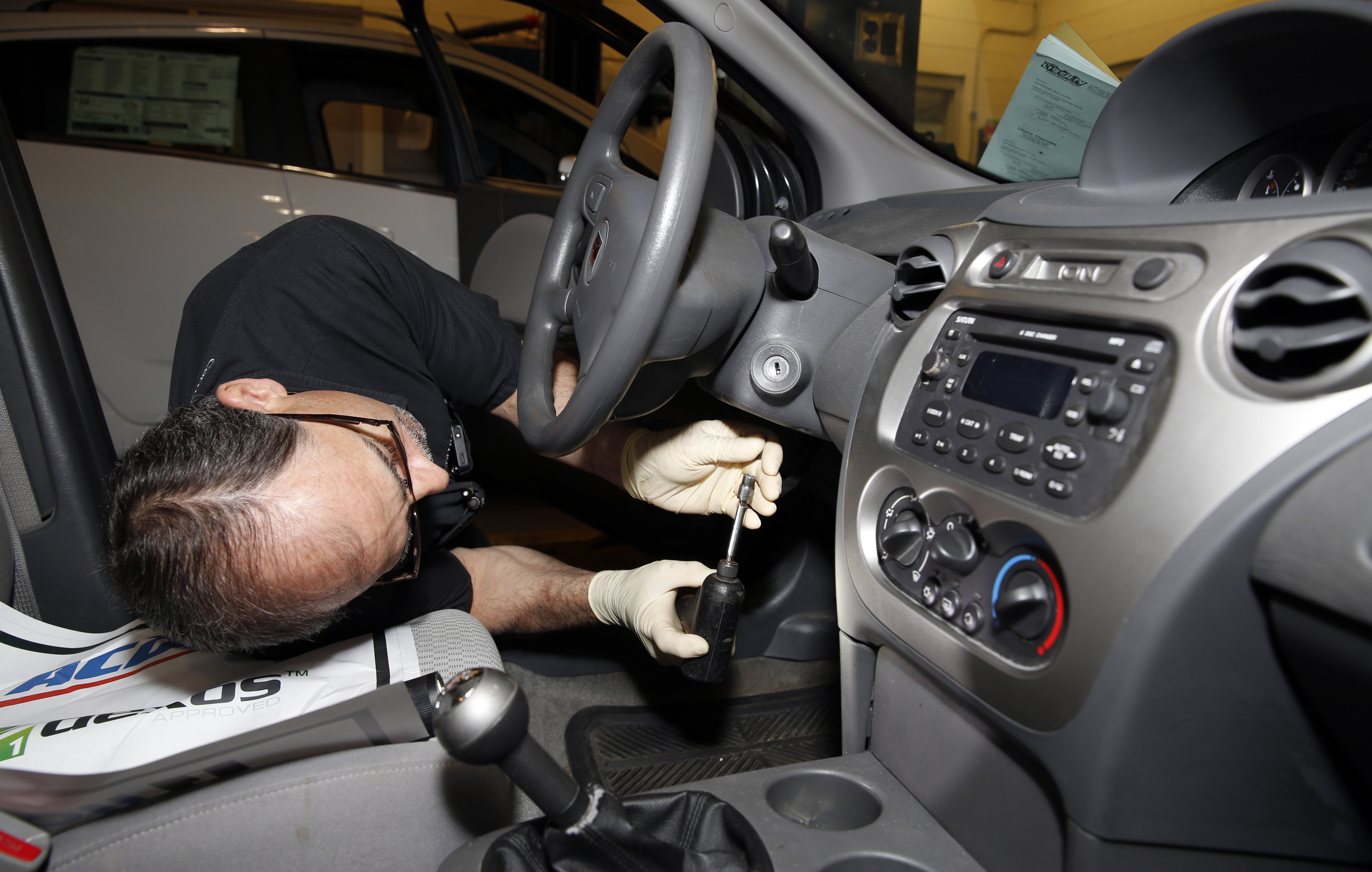 Shop foreman John Chapman performs a service recall on a General Motors Co. (GM) 2005 Saturn Ion at Liberty Chevrolet in New Hudson, Michigan, U.S., on Friday, April 25, 2014.