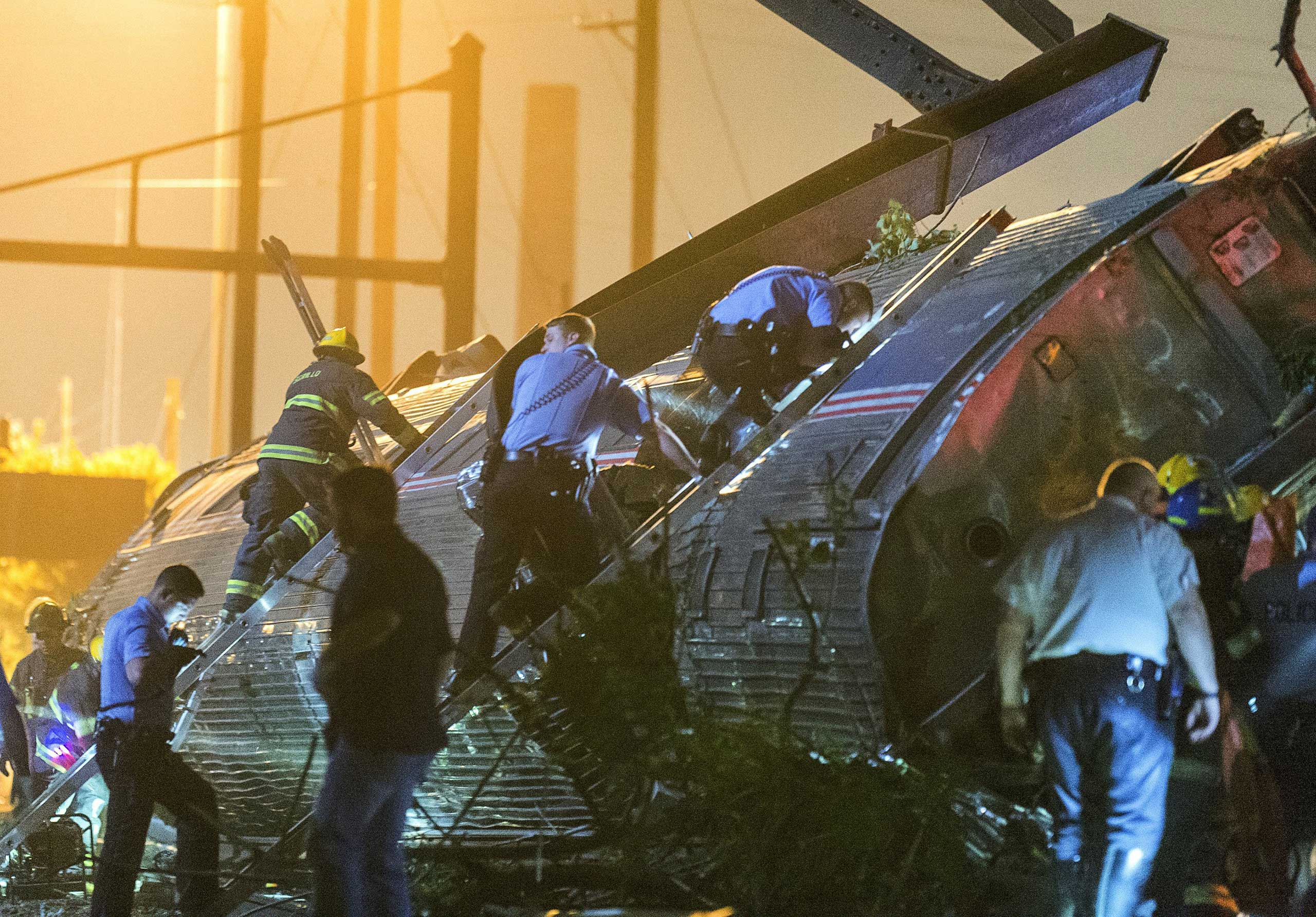Rescue workers climb into the wreckage of a derailed Amtrak train to search for victims in Philadelphia on May 12, 2015.