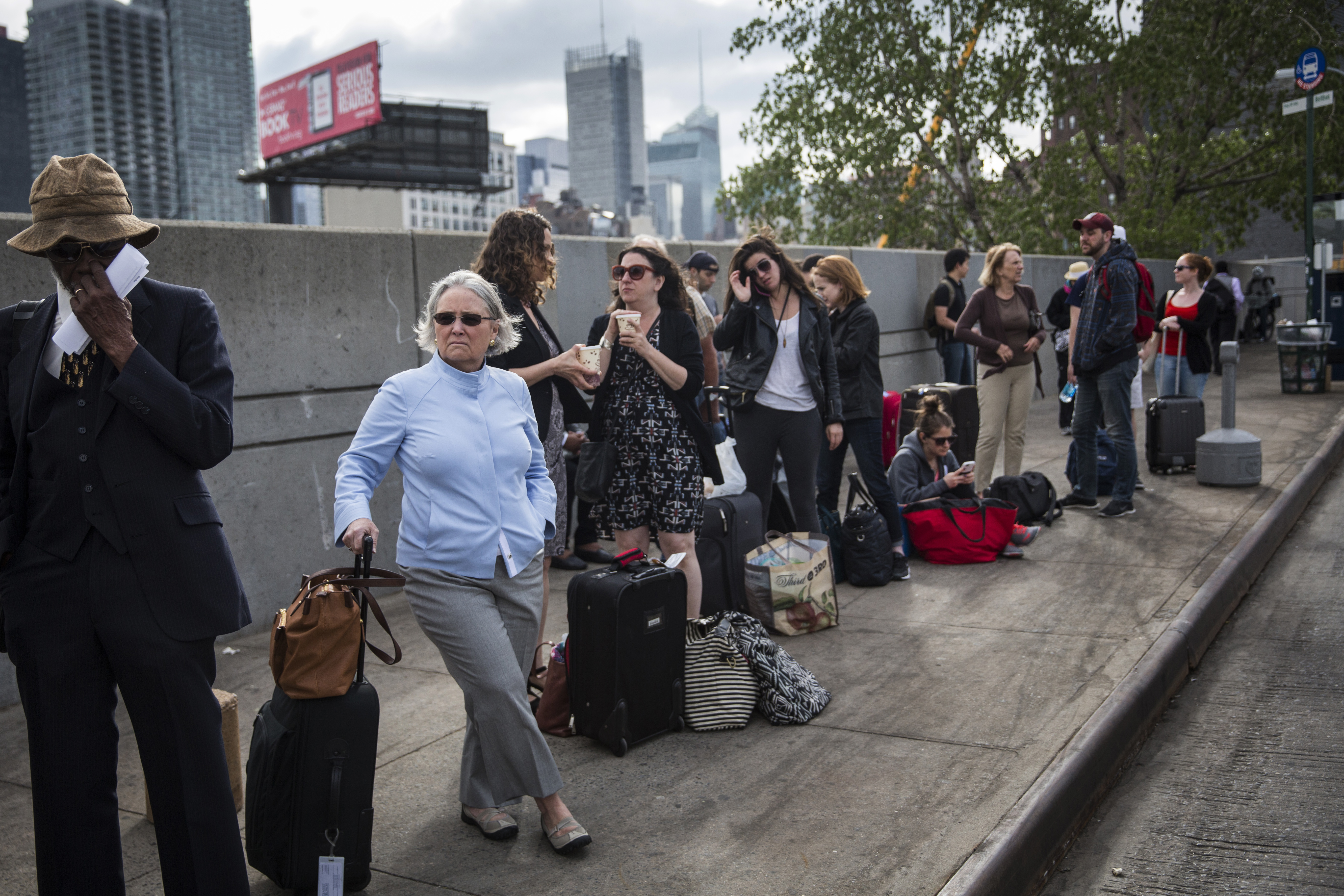 Passengers wait for a bus from New York to Washington D.C. on Wednesday in New York City after an Amtrak train crash in Philadelphia forced train service to be suspended between New York, Philadelphia and Washington D.C.