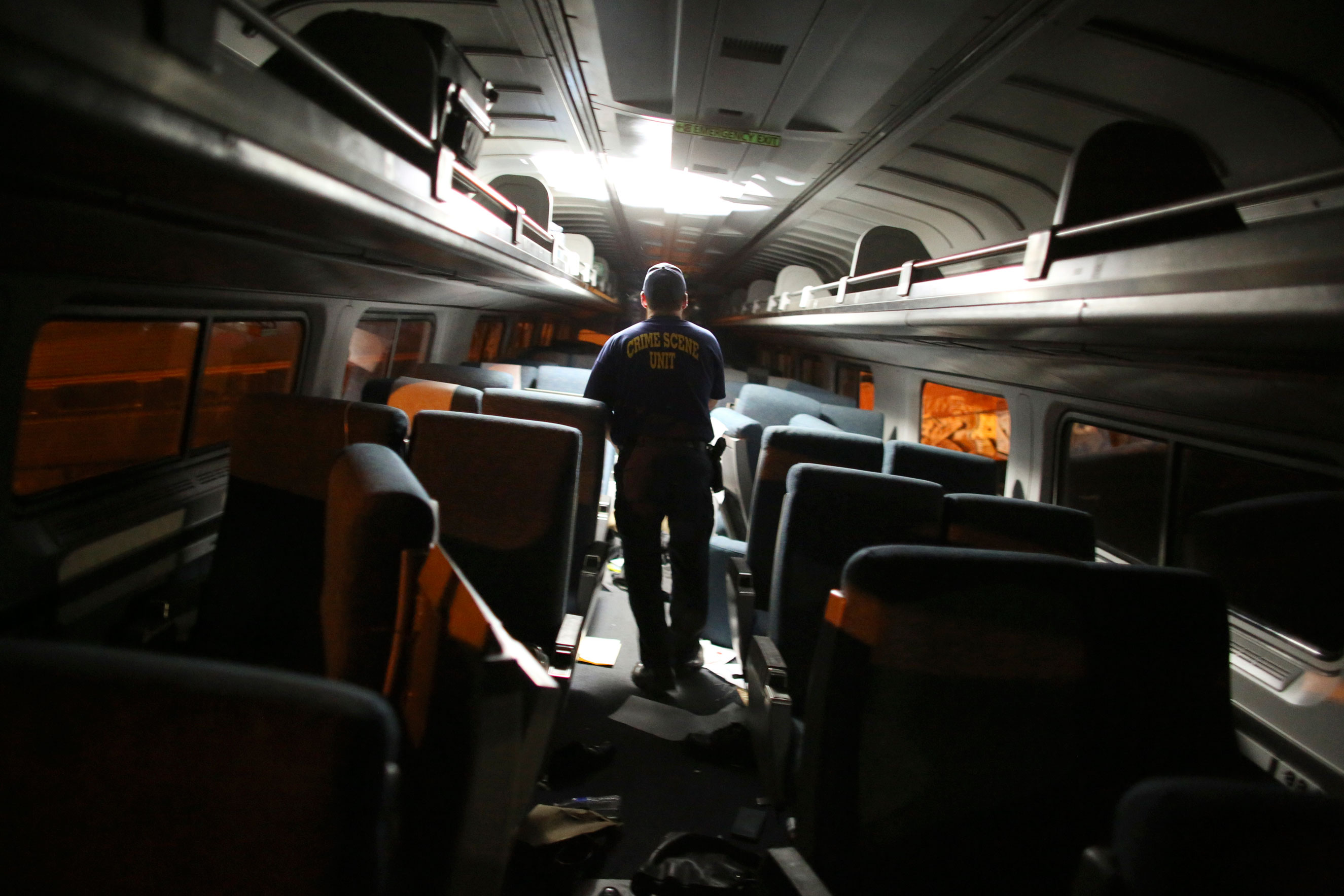 A crime scene investigator looks inside a train car after a train wreck on May 12, 2015, in Philadelphia.